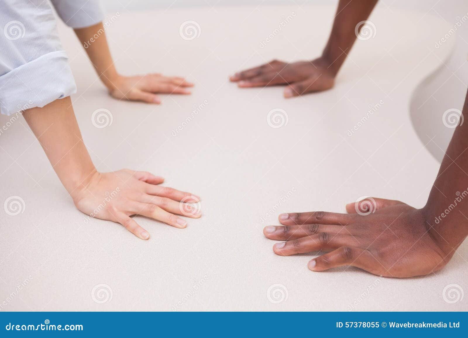 Toevallige bedrijfscollega s met handen op bureau