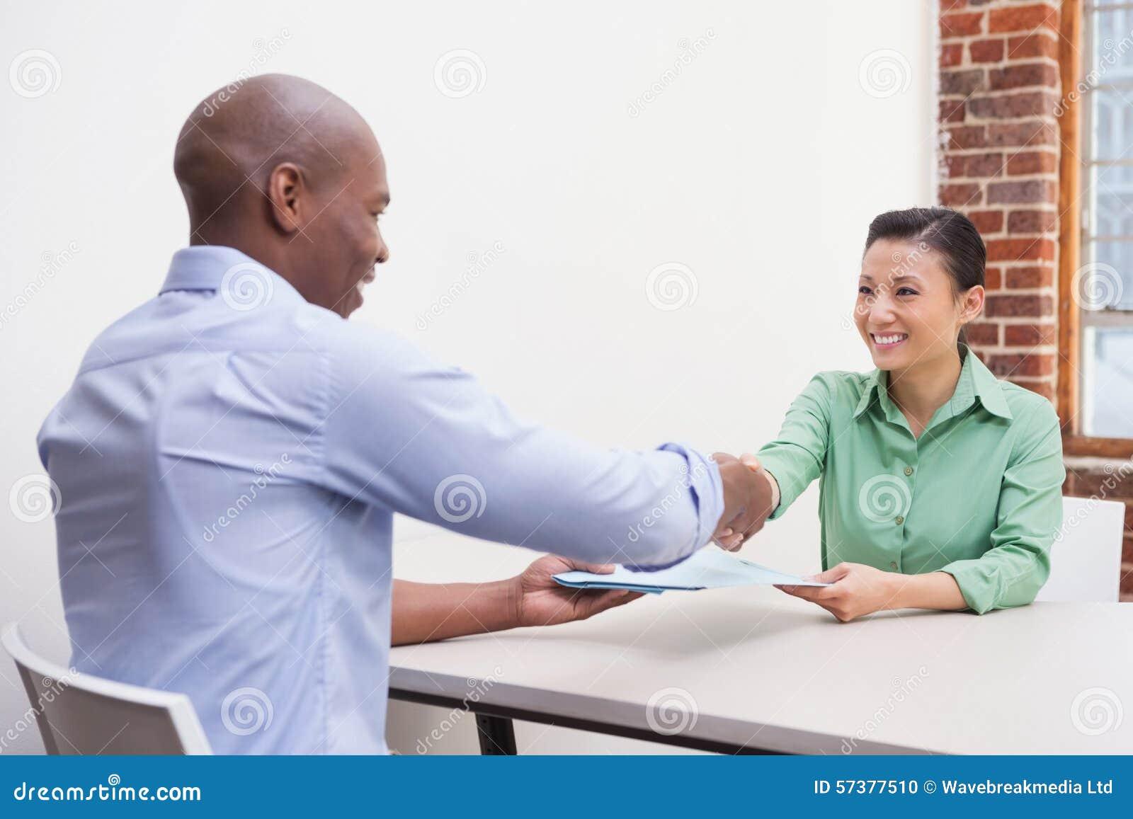 Toevallige bedrijfsmensen die handen schudden bij bureau