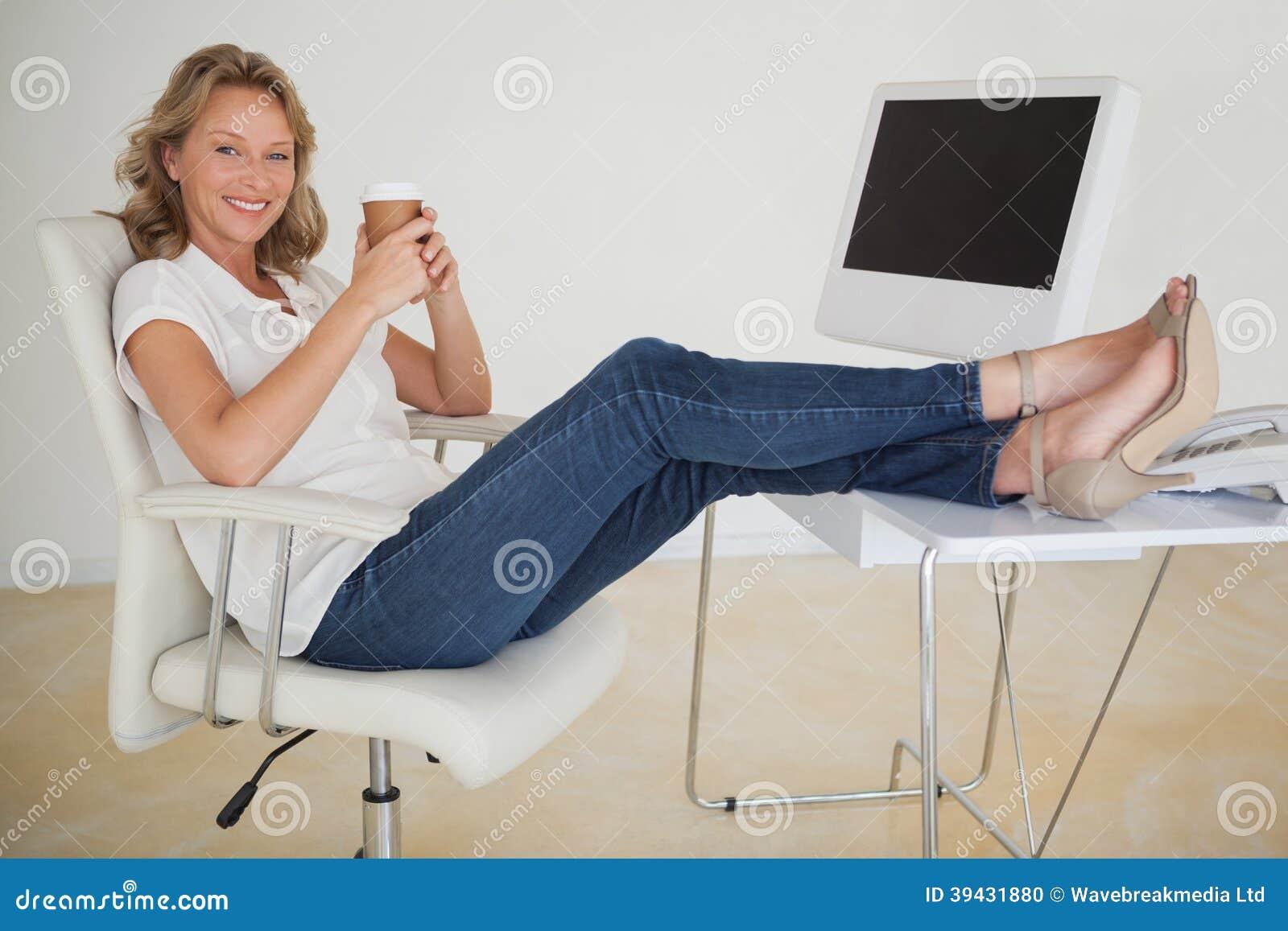 Toevallige onderneemster die een koffie met haar voeten heeft omhoog bij bureau