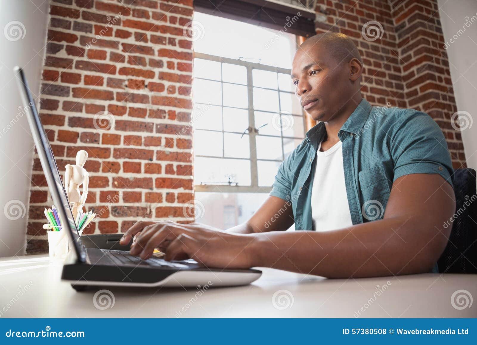 Toevallige zakenman die aan laptop bij bureau werken
