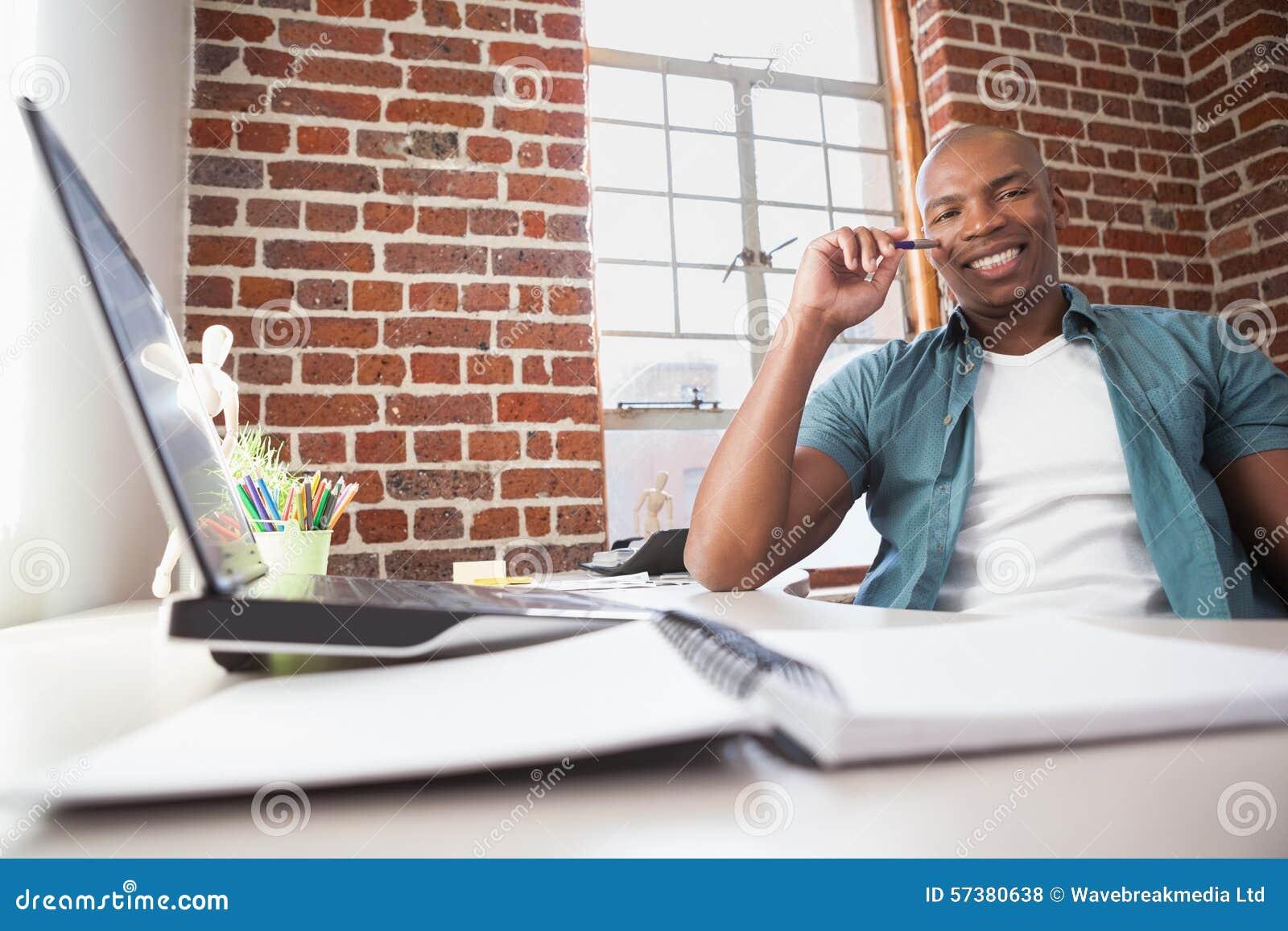 Toevallige zakenman die bij zijn bureau glimlachen