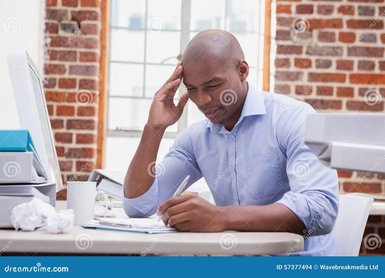 Toevallige zakenman die bij zijn bureau schrijven