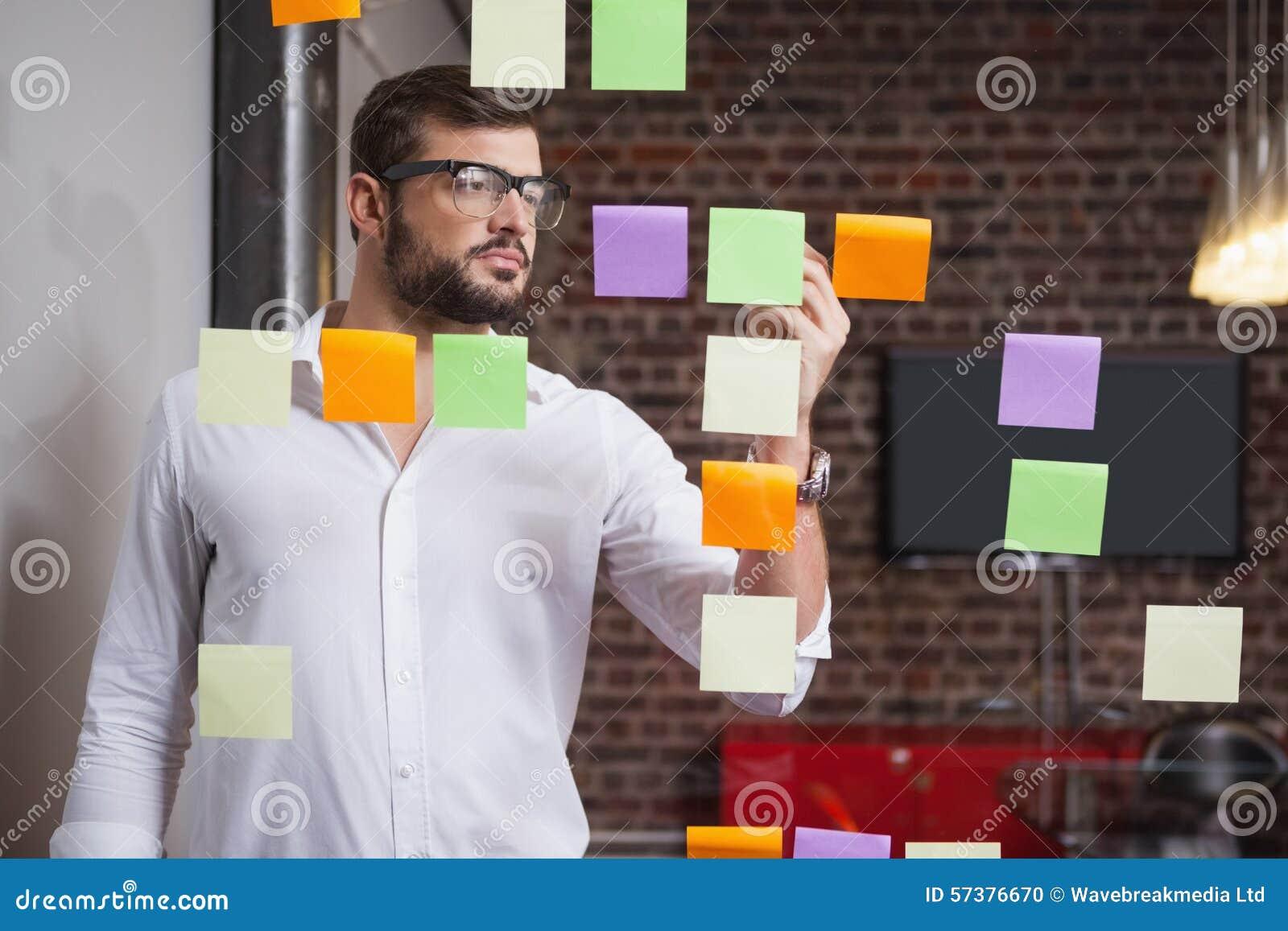 Toevallige zakenman die op kleverige nota s schrijven