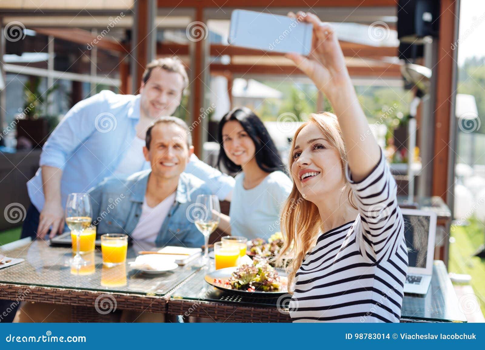 Joyful nice woman taking a photo of her friends