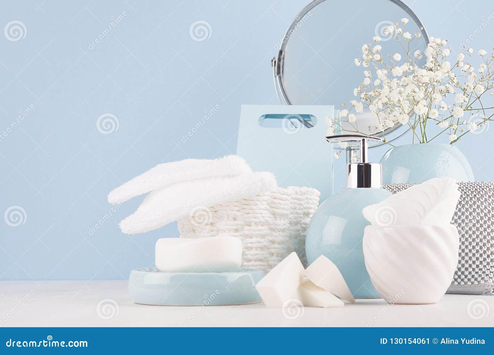 Toilettafel met cirkelspiegel, kosmetische zilveren toebehoren en witte kleine bloemen in ceramische pastelkleur blauwe vaas op w