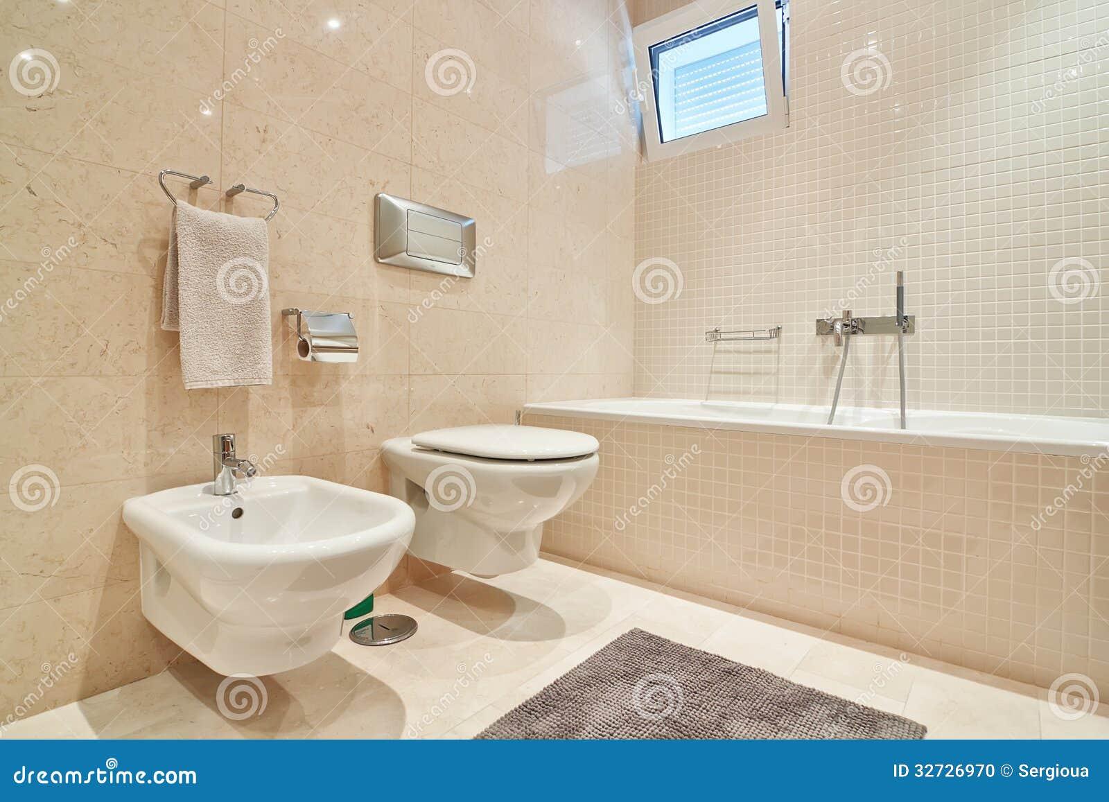 Toilette moderna con le piastrelle di ceramica ed il bagno