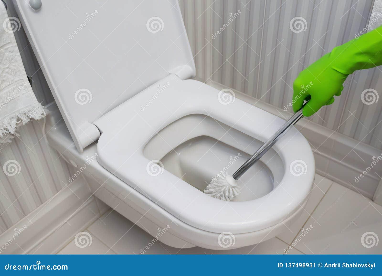 Toilettensch?sselreinigung Reiniger in den grünen Gummihandschuhen