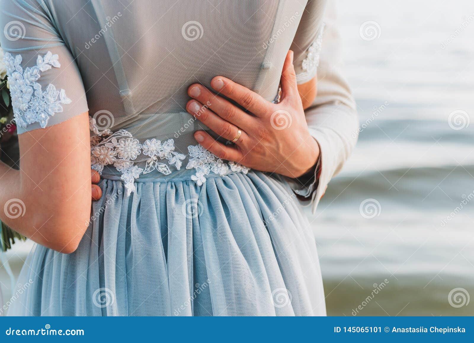 Toilettez avoir sa main sur la taille de sa jeune mariée, se tenant sur une plage