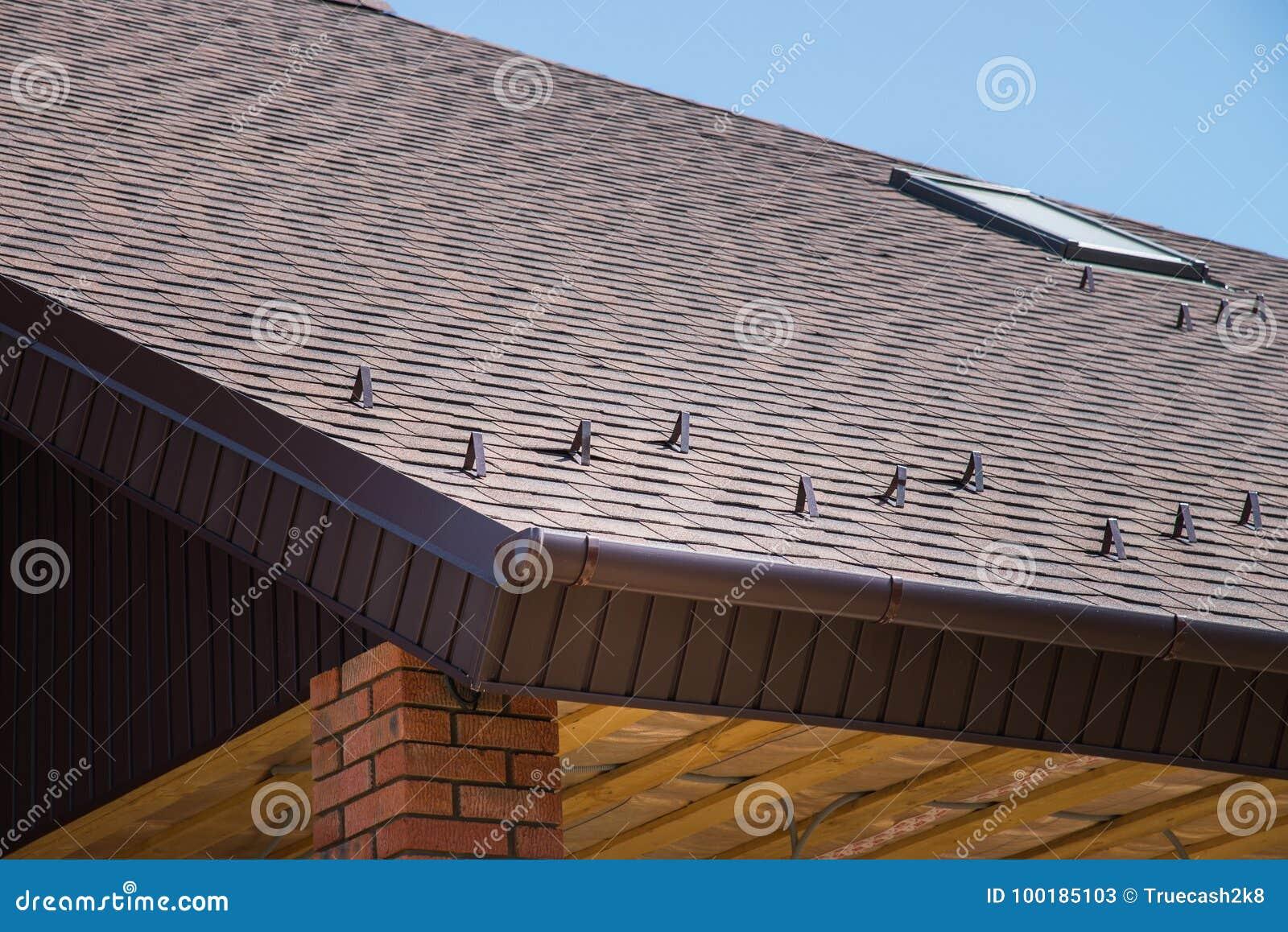 toit brun carrelé de nouvelle maison avec le débordement, protection