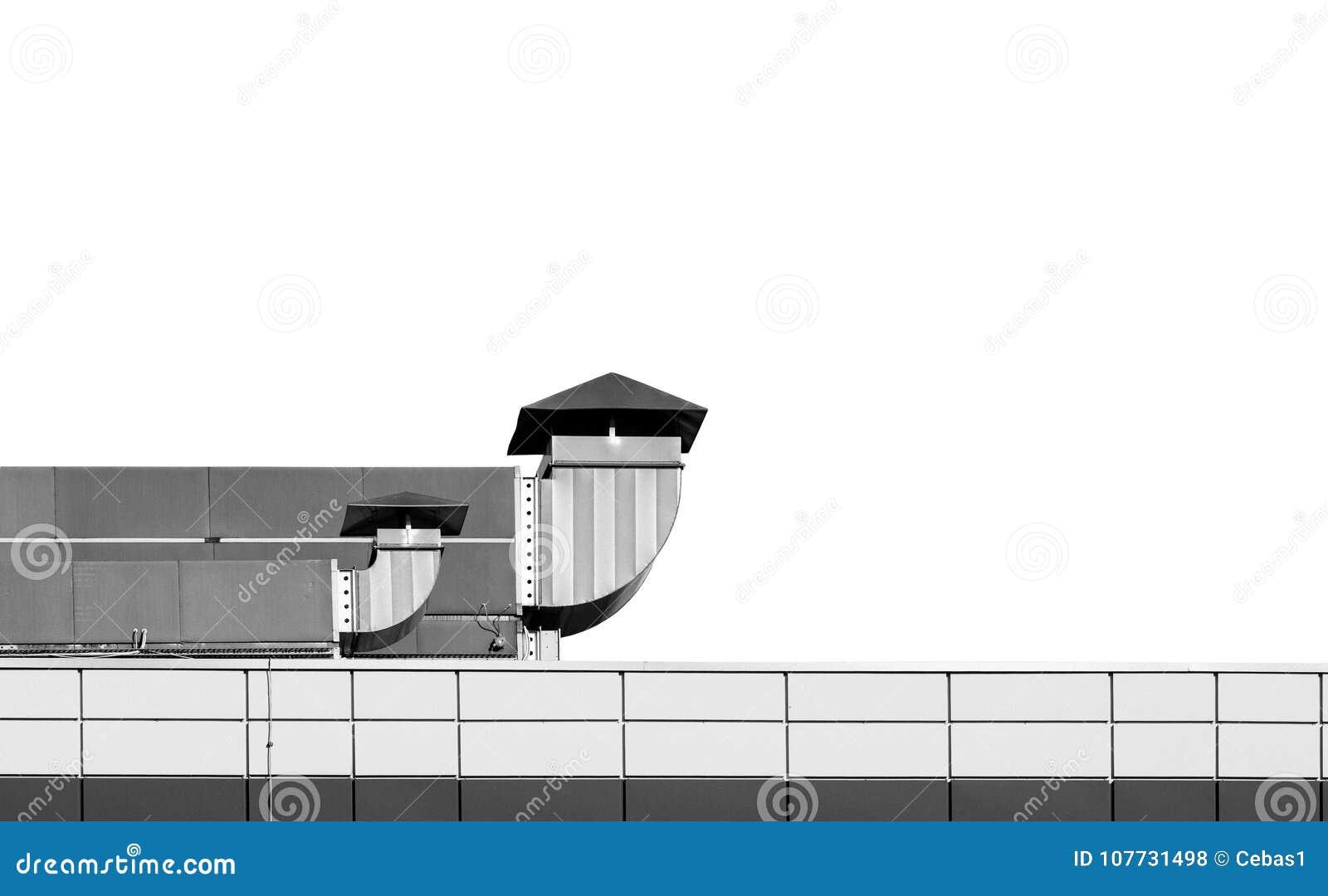Toit de bâtiment industriel avec des cheminées de ventilation sur le dos de blanc