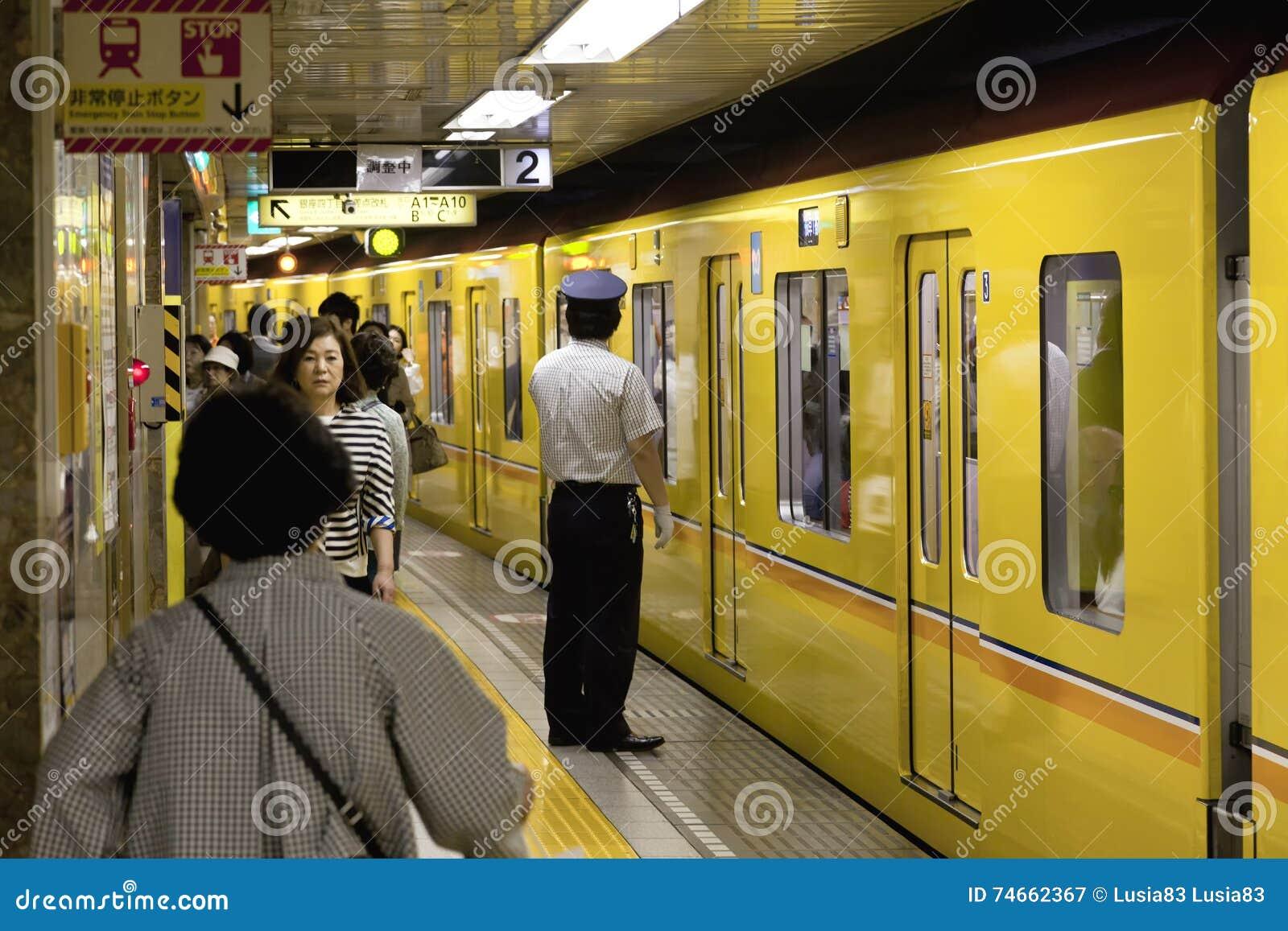 TOKYO CIRCA MAG, 2016: Passagiers die door metro van Tokyo reizen Bedrijfsmensen die aan het werk door openbaar vervoer in spitsu