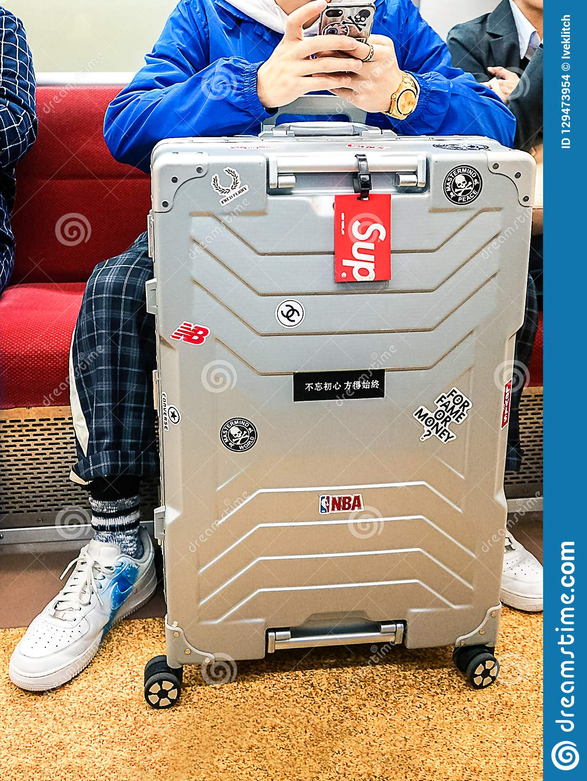 Tokyo, Japan 10.02.2018 bright stylish aluminum suitcase with stickers next to fashionably dressed young man sitting in subway