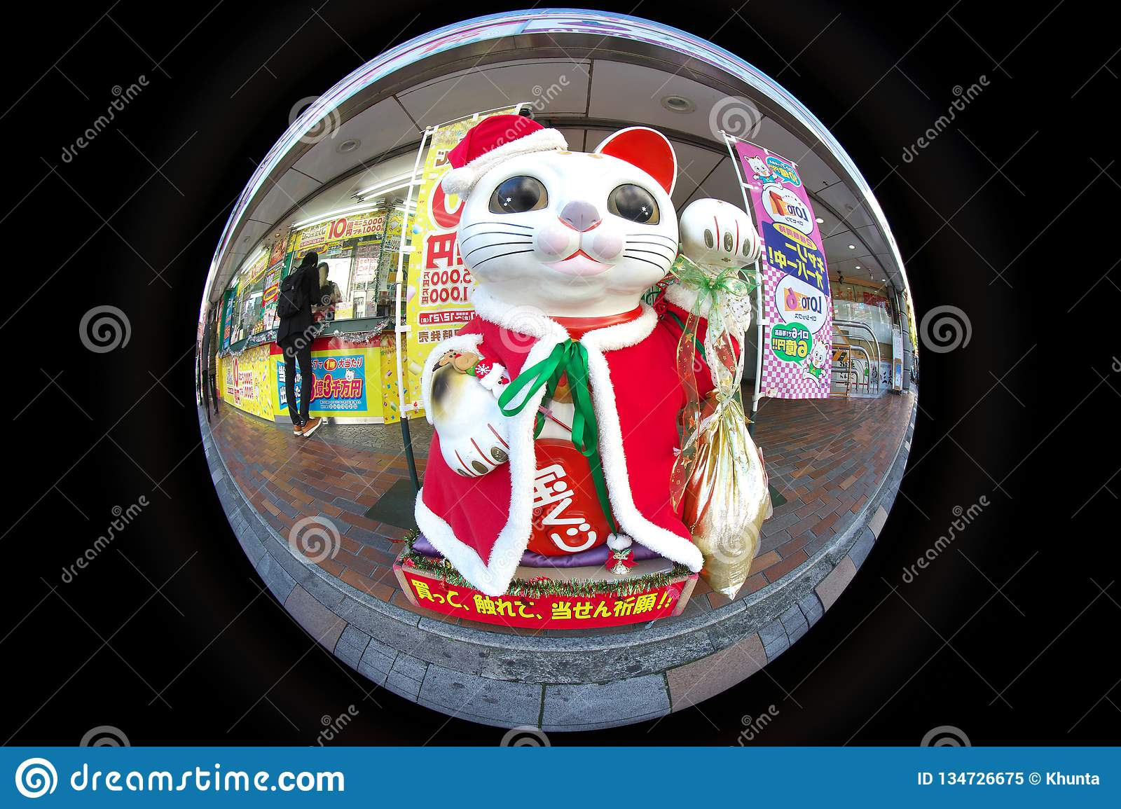 A big beckoning cat or a lucky cat in front of lottery shop