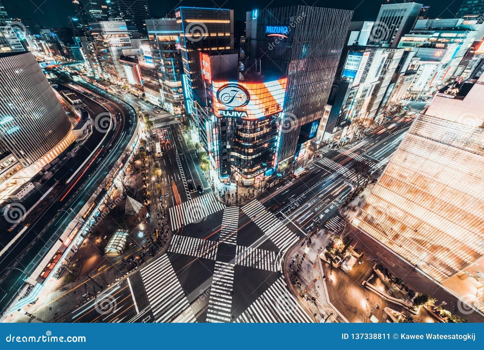 Tokyo Japan - Januari 13, 2019: Flyg- nattsikt för Cityscape av genomskärningen för väg för Ginza sebraövergångsställe med biltra