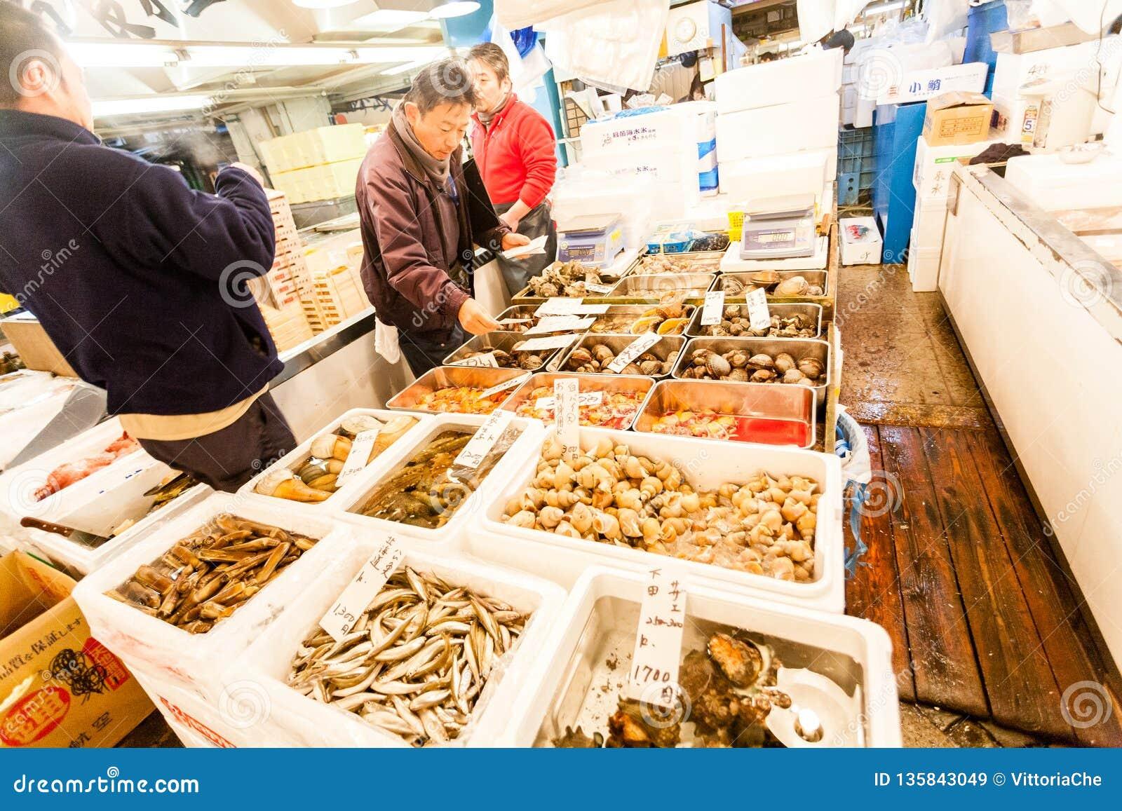 Tokyo, Japan - January 15, 2010: The first customers buy fresh fish at early morning in Tsukiji Fish Market
