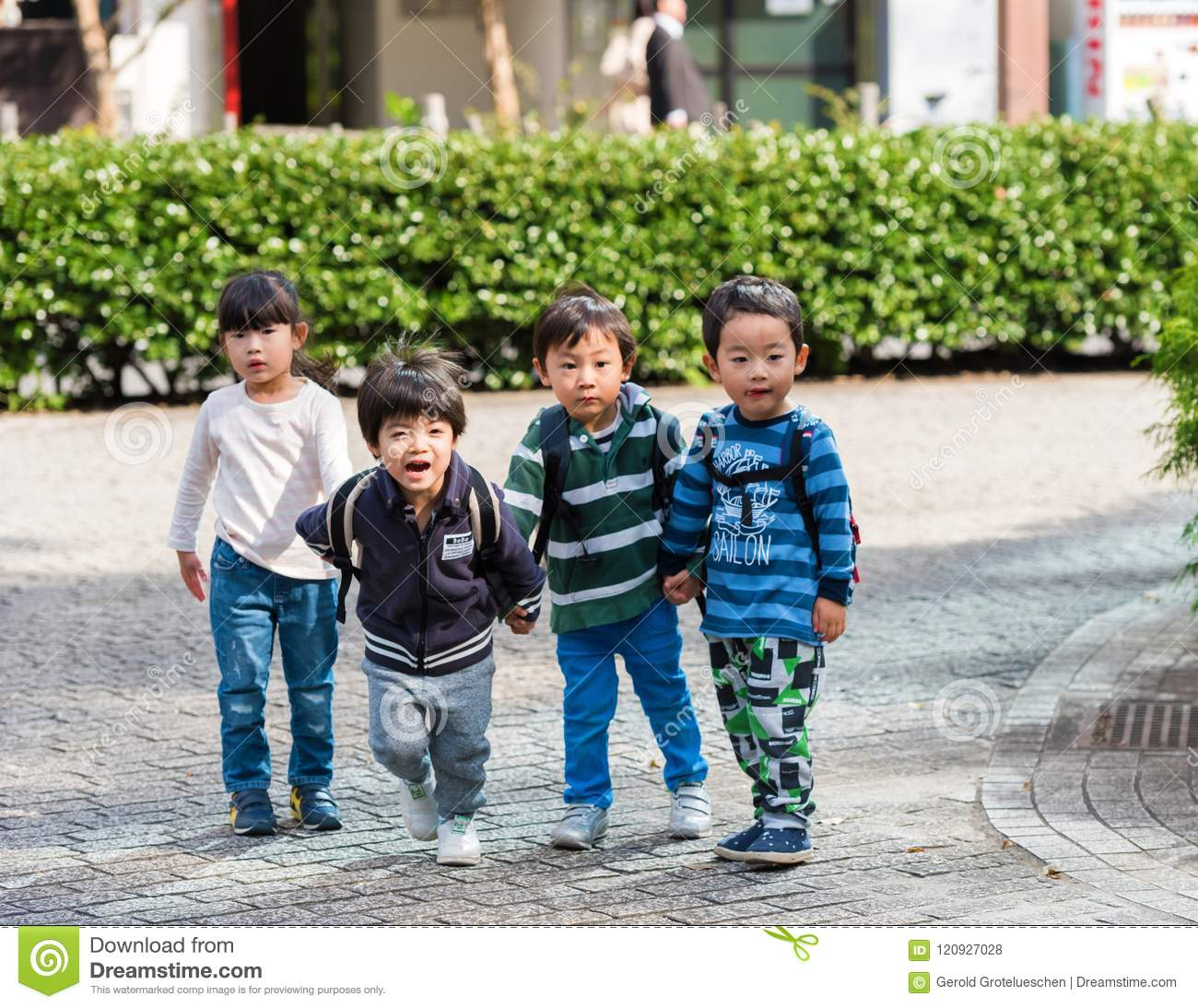 TOKYO, JAPAN - NOVEMBER 7, 2017: Four children in a city park. Copy space for text.