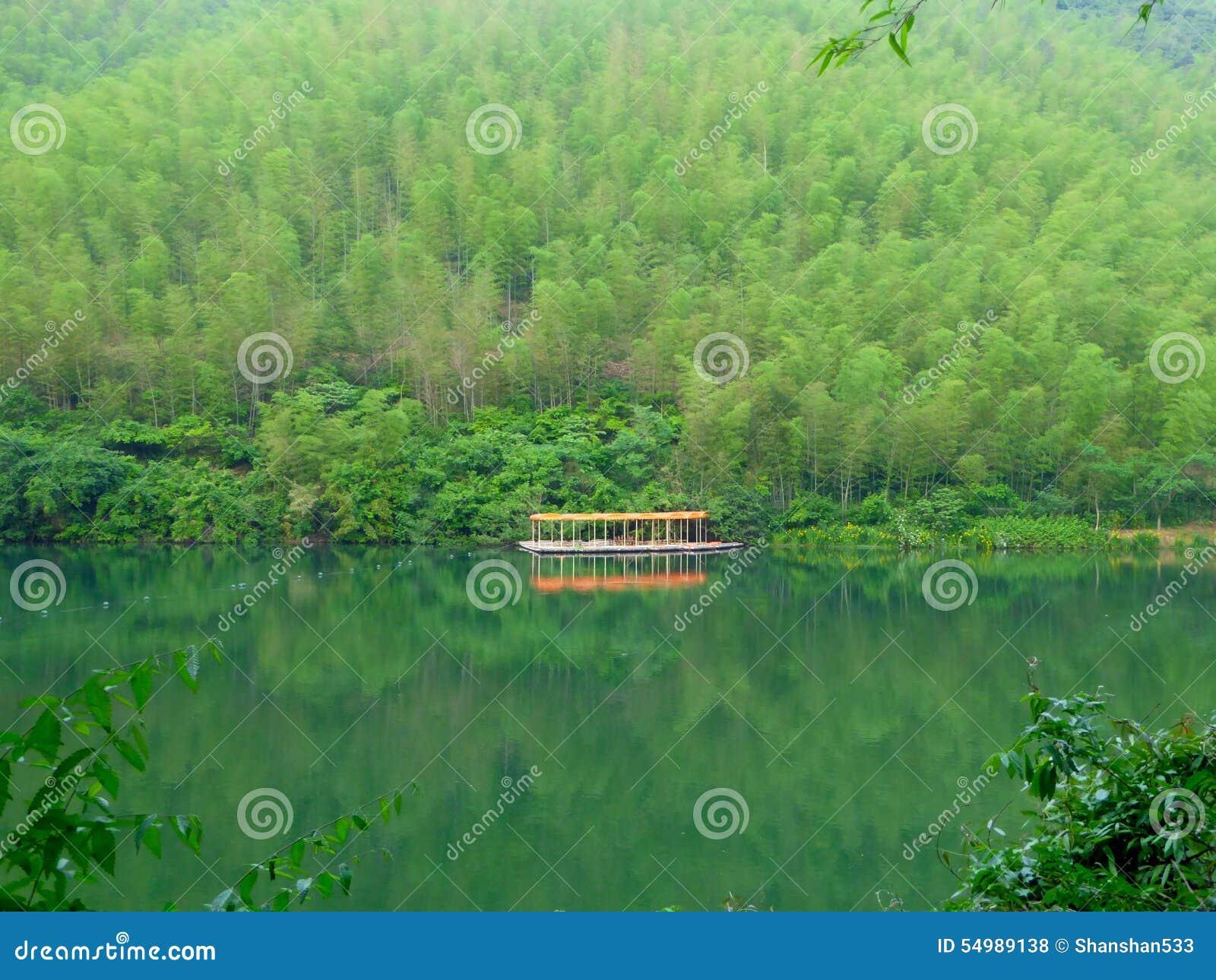 Toldos de una fila en el medio del lago y de las montañas