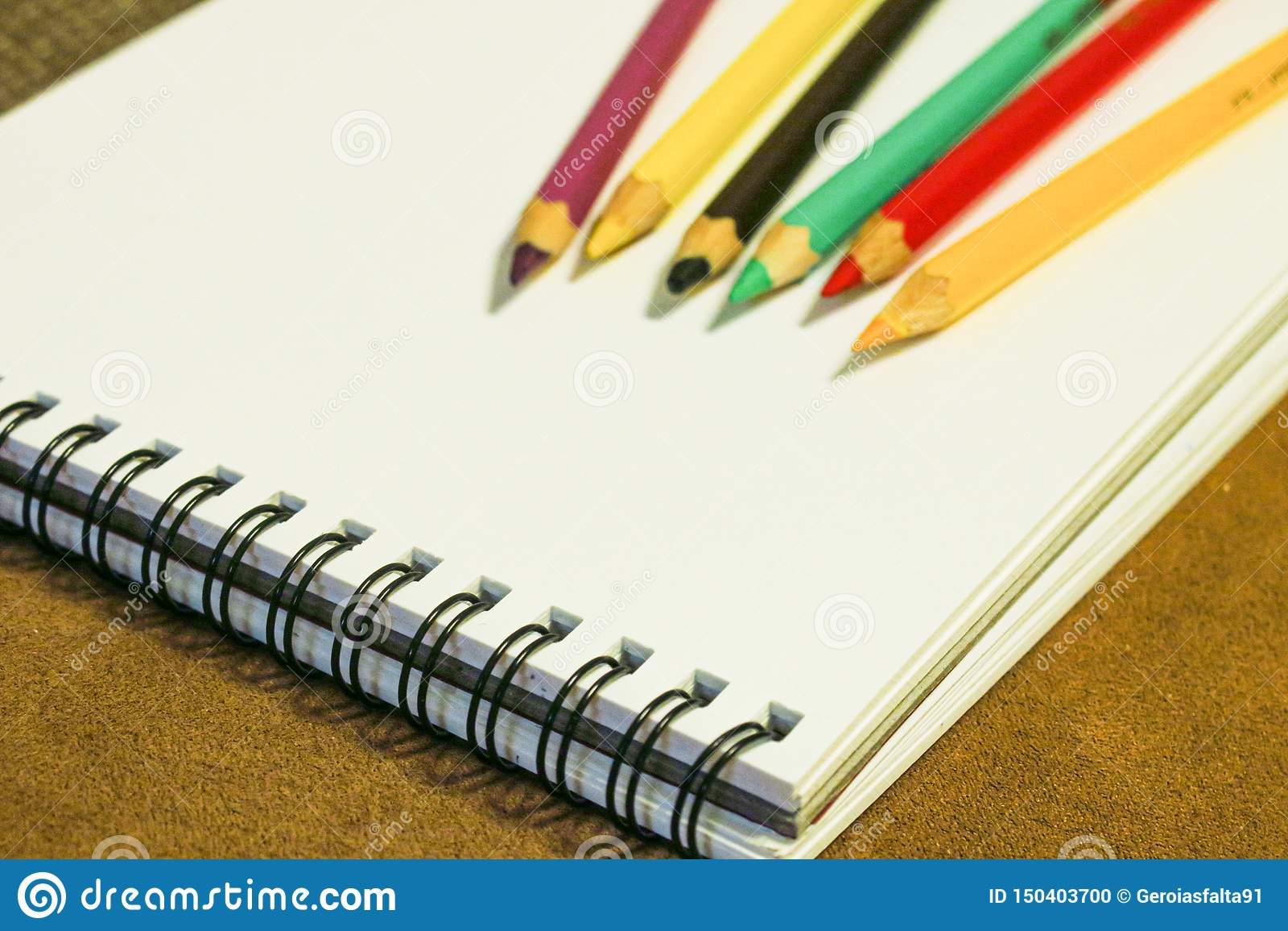 Tom anteckningsbok och färgrika blyertspennor på brun bakgrund, målningmaterial
