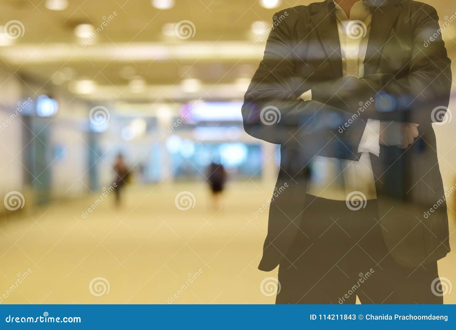 Tom da cor do borrão do fundo morno na manhã a passagem dentro da construção lá é pessoa O primeiro plano é um homem que veste um