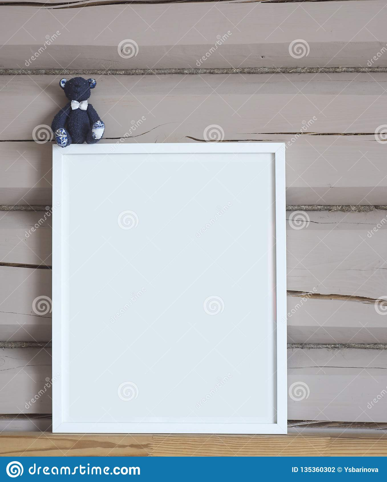 Tom inre affisch för vitbok, med den blåa björnleksaken, isolerad vertikal åtlöje upp med ramen på beige träväggbakgrund, barn