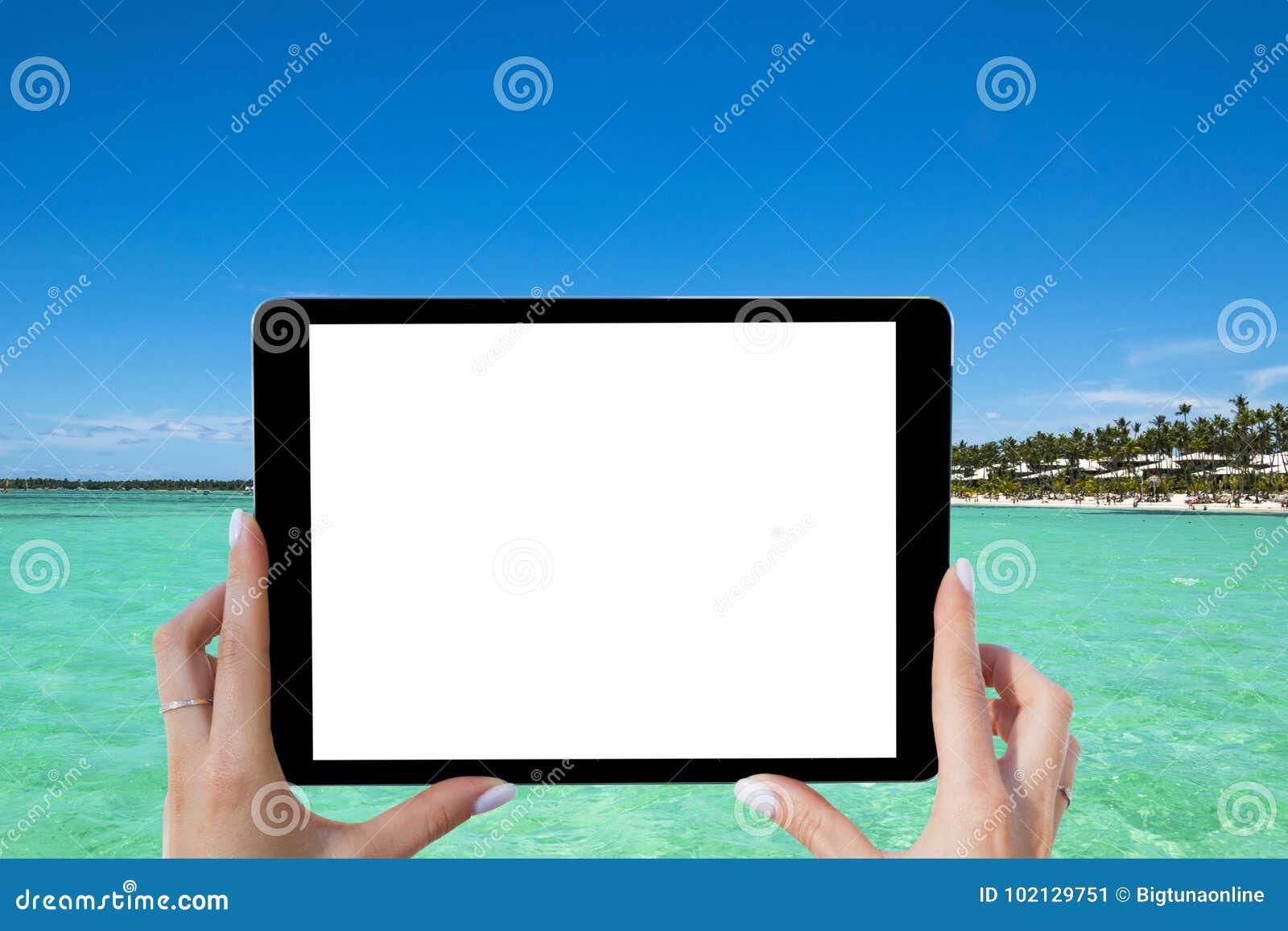 Tom tom minnestavladator i händerna av flickan på den tropiska turkoshavstranden Isolerad vit skärm Töm utrymme