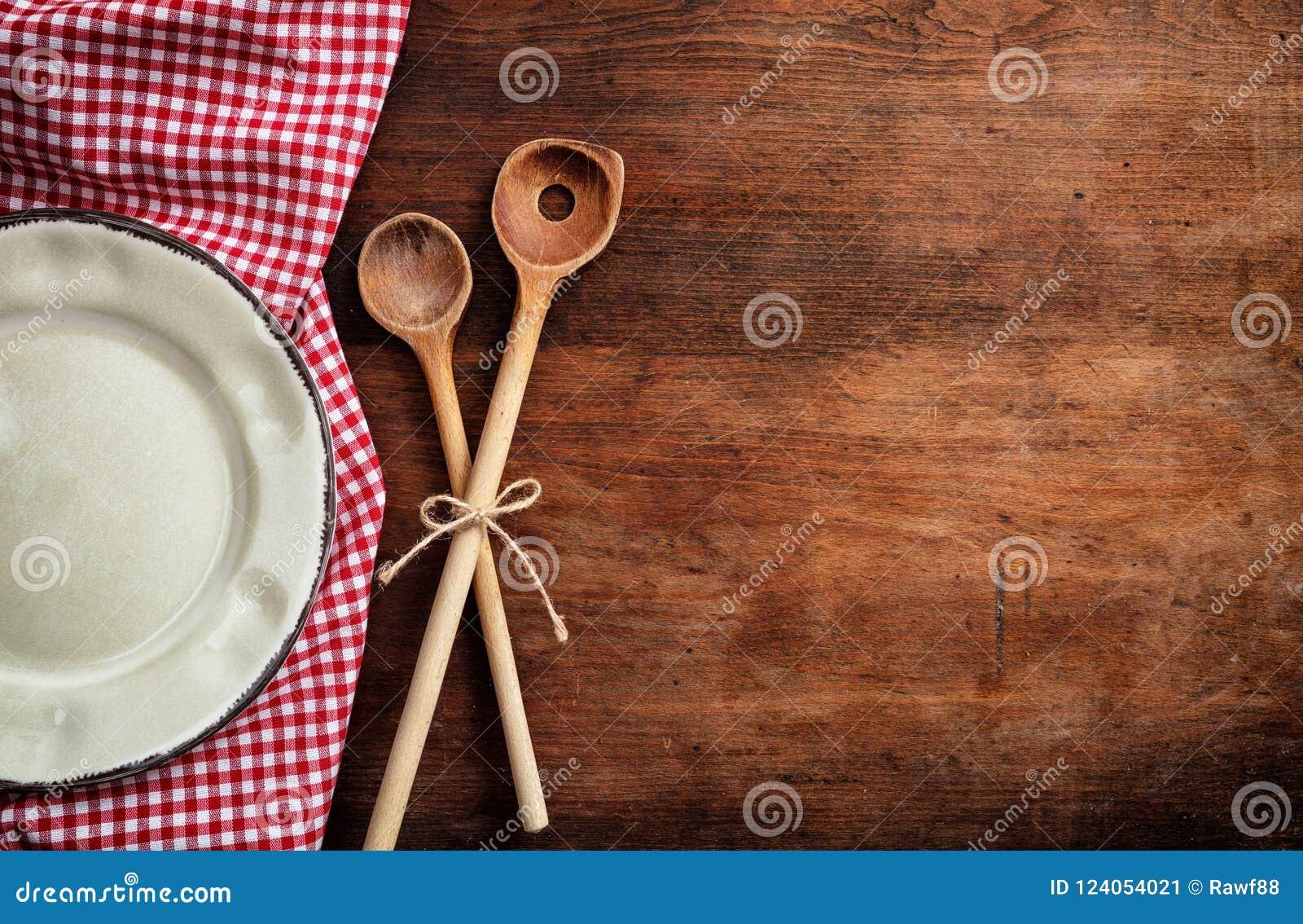 Tom platta, köksgeråd och röd bordduk på trätabellen, bästa sikt, kopieringsutrymme