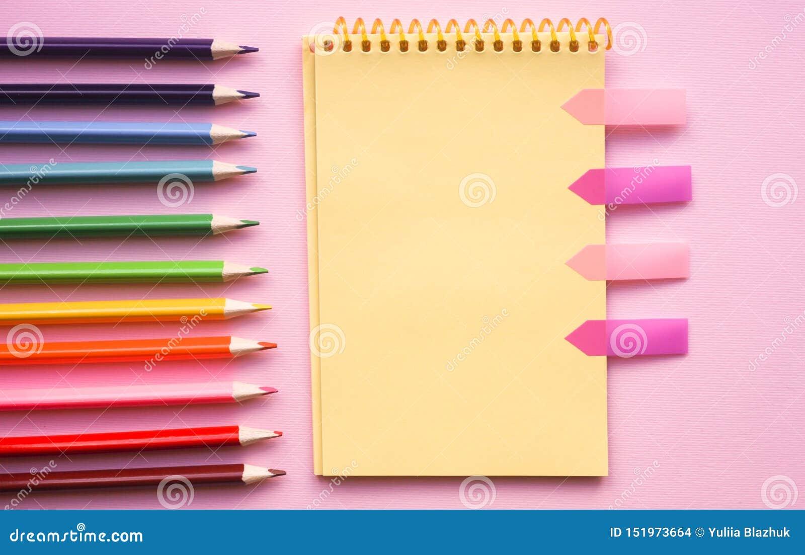 Tom sida av det vertikala spiral skissa blocket med färgpennor på rosa bakgrund