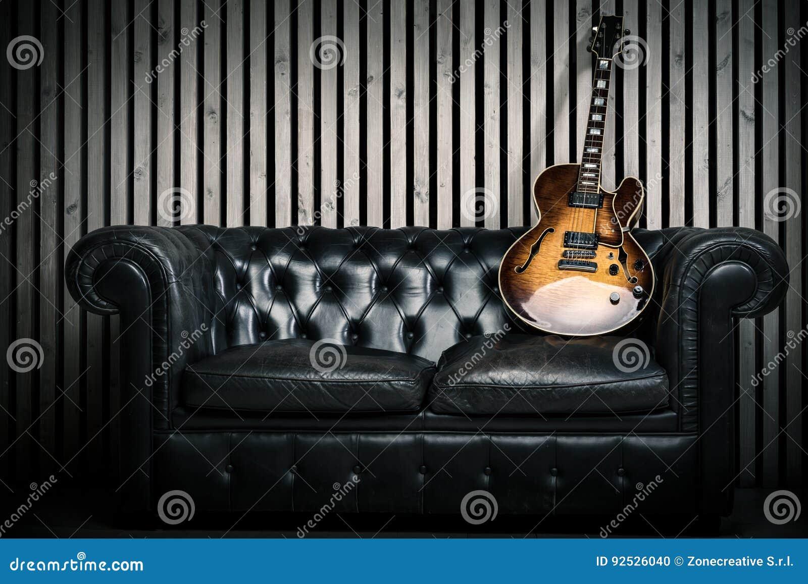 Tom tappningsoffa och elektrisk gitarr med modern wood bakgrund för vägginspelningstudio Musikbegrepp med inget