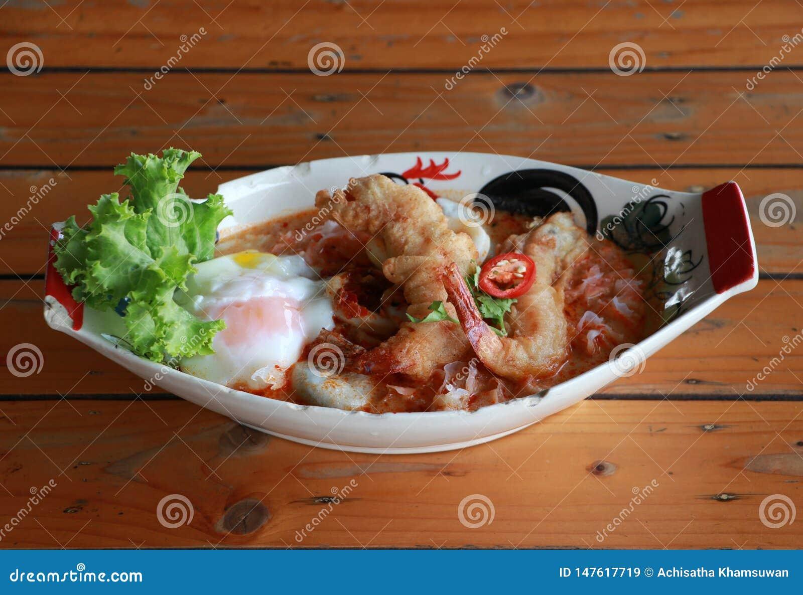 Tom Yum Goong Spicy Sour Soup con el huevo curruscante frito de la gamba y de la lava en el cuenco oval
