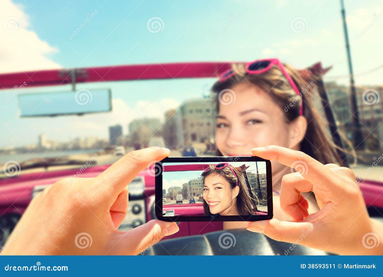 Tomando imagens com o telefone esperto da mulher no carro