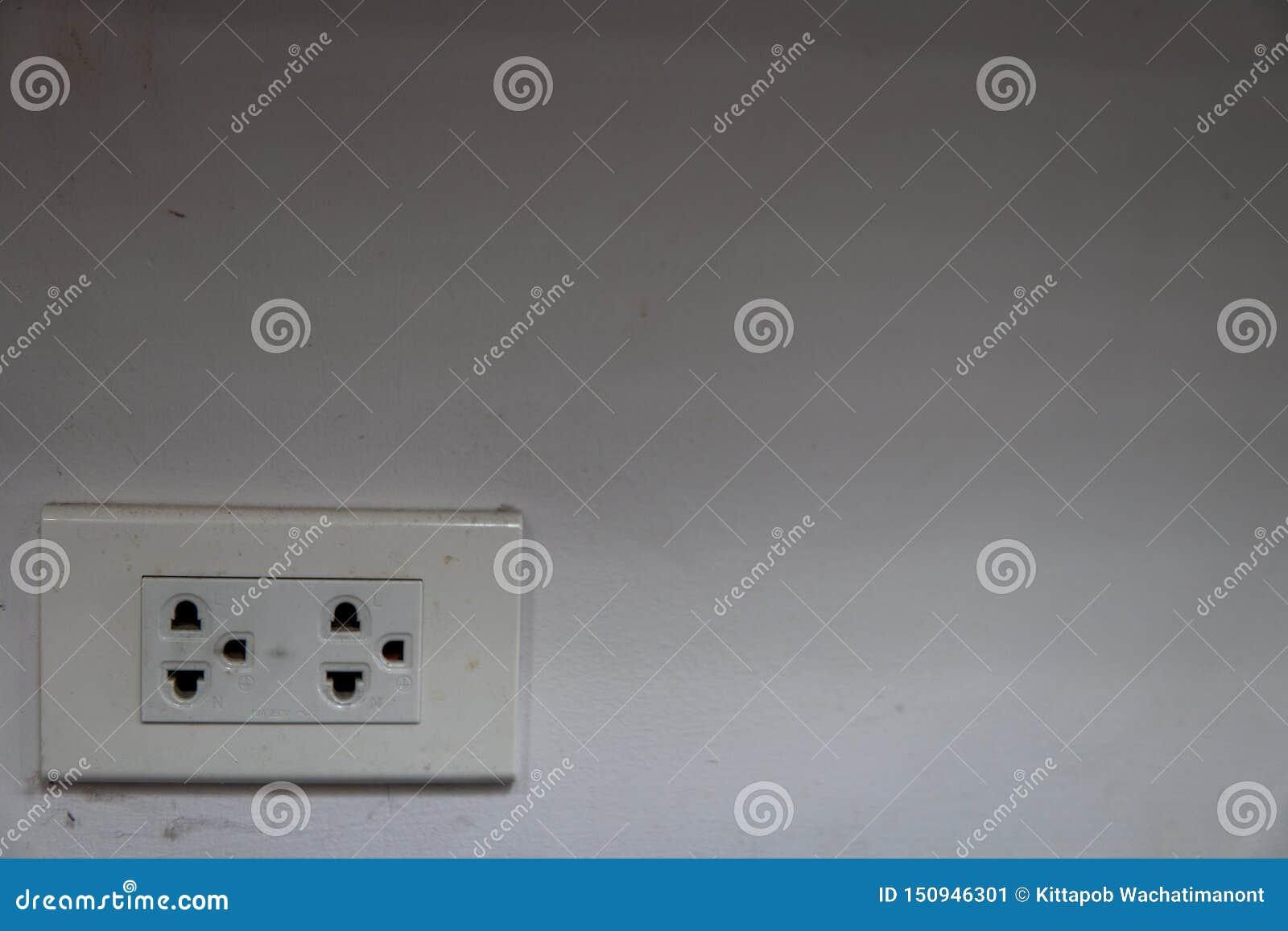 Tomas de corriente con la araña ondulada en una pared blanca sucia en una esquina del cuarto