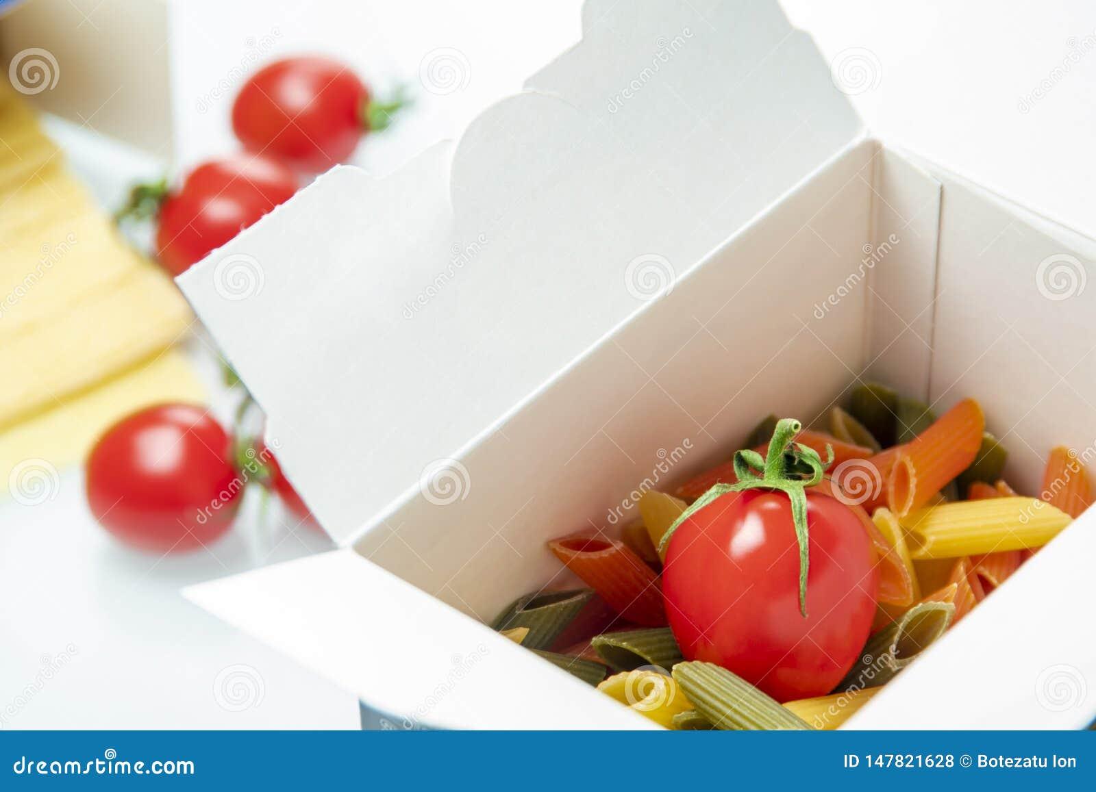 Tomate colocado en una caja de las pastas del color