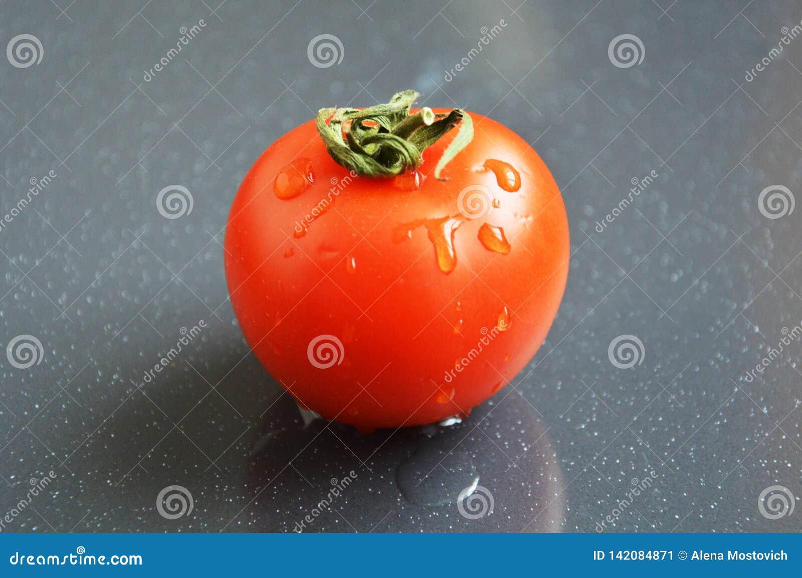 Tomate vermelho suculento no fundo cinzento