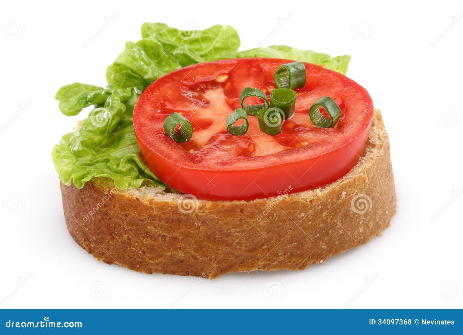 Tomate y una rebanada de pan del trigo integral