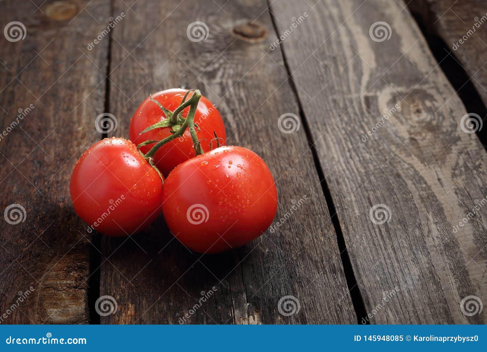 Tomaten, een bos van rode rijpe tomaten op een houten achtergrond