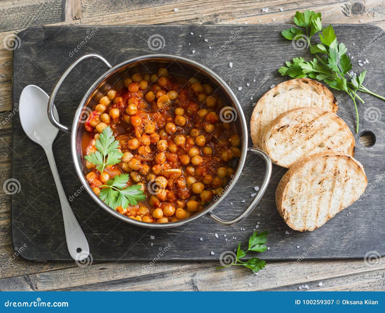 Tomatensaus gesmoorde kekers in een pot, en geroosterd brood Heerlijke vegetarische lunch op een rustieke houten achtergrond