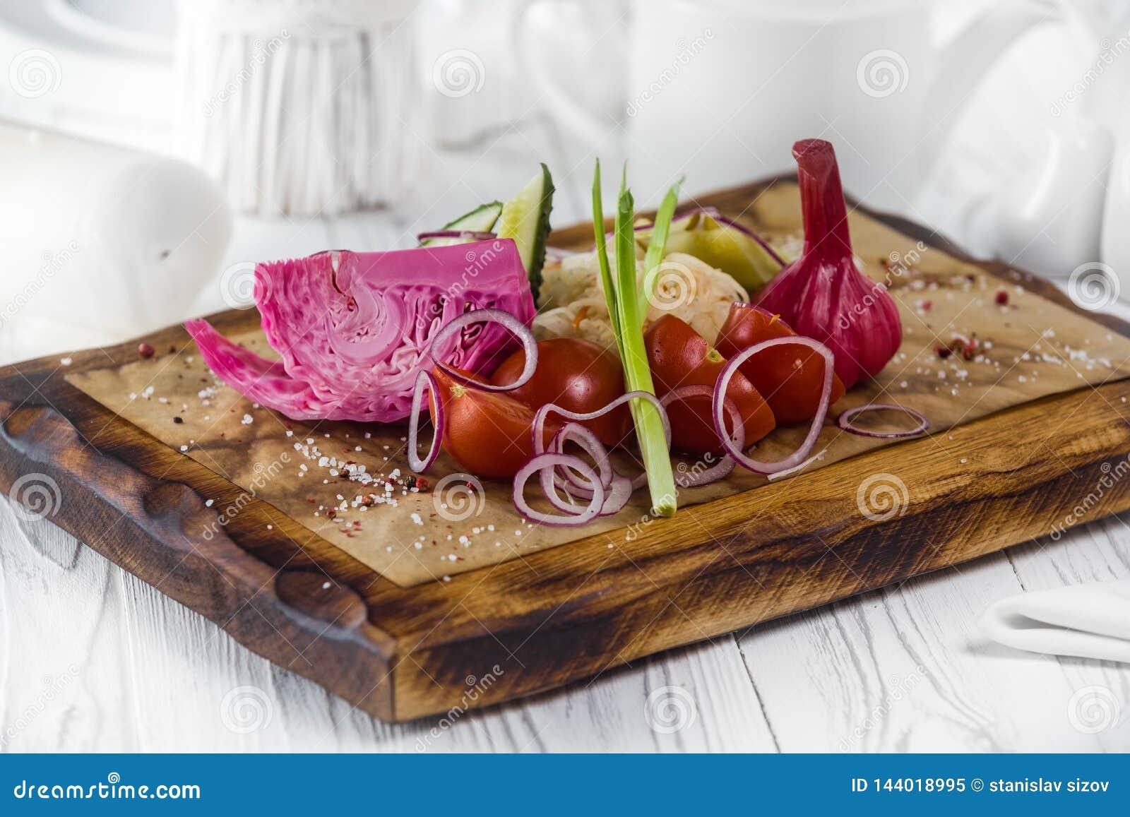Tomater, vitlök och lök Olika nya och inlagda grönsaker på ett bräde