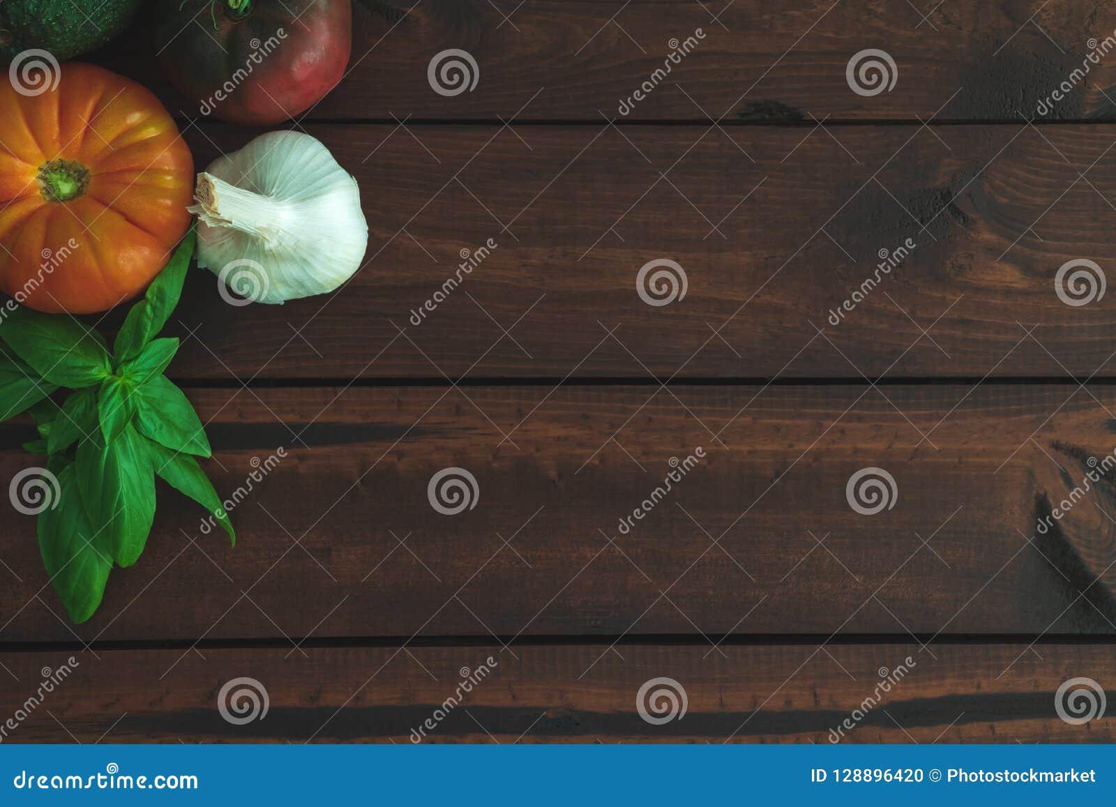 Tomates, ail, avocat et basilic d héritage sur un conseil brun