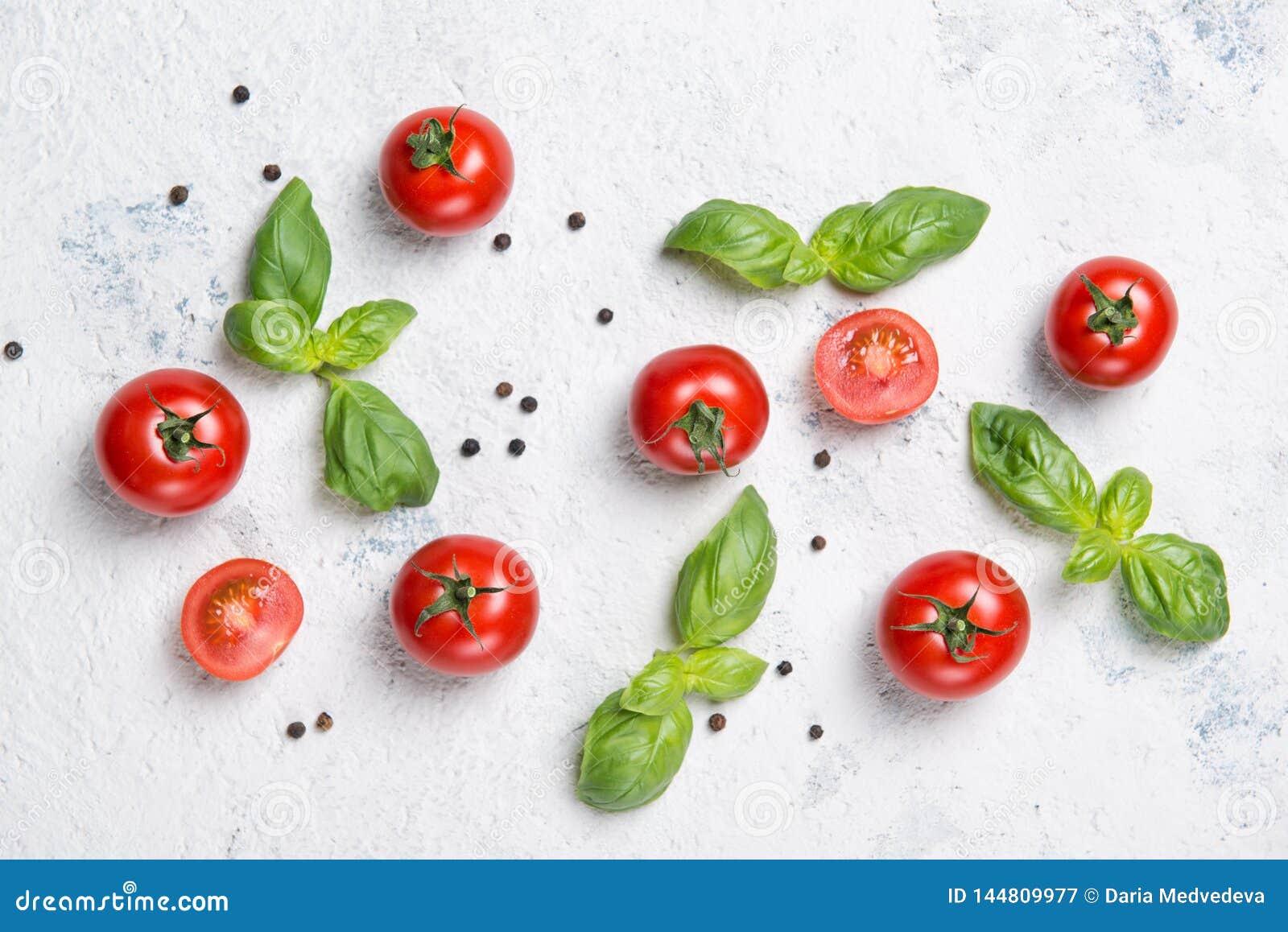 Tomates-cerises fraîches avec les feuilles de basilic et le poivre noir sur une table en pierre, modèle végétal, vue supérie