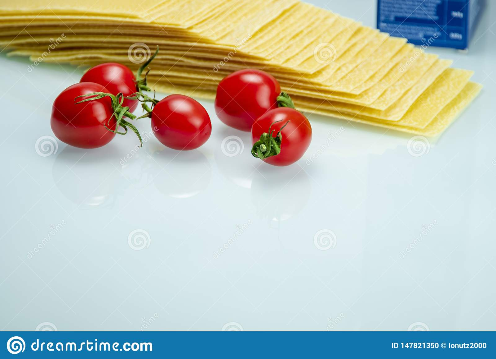 Tomates con lasañas sobre el vidrio reflexivo blanco