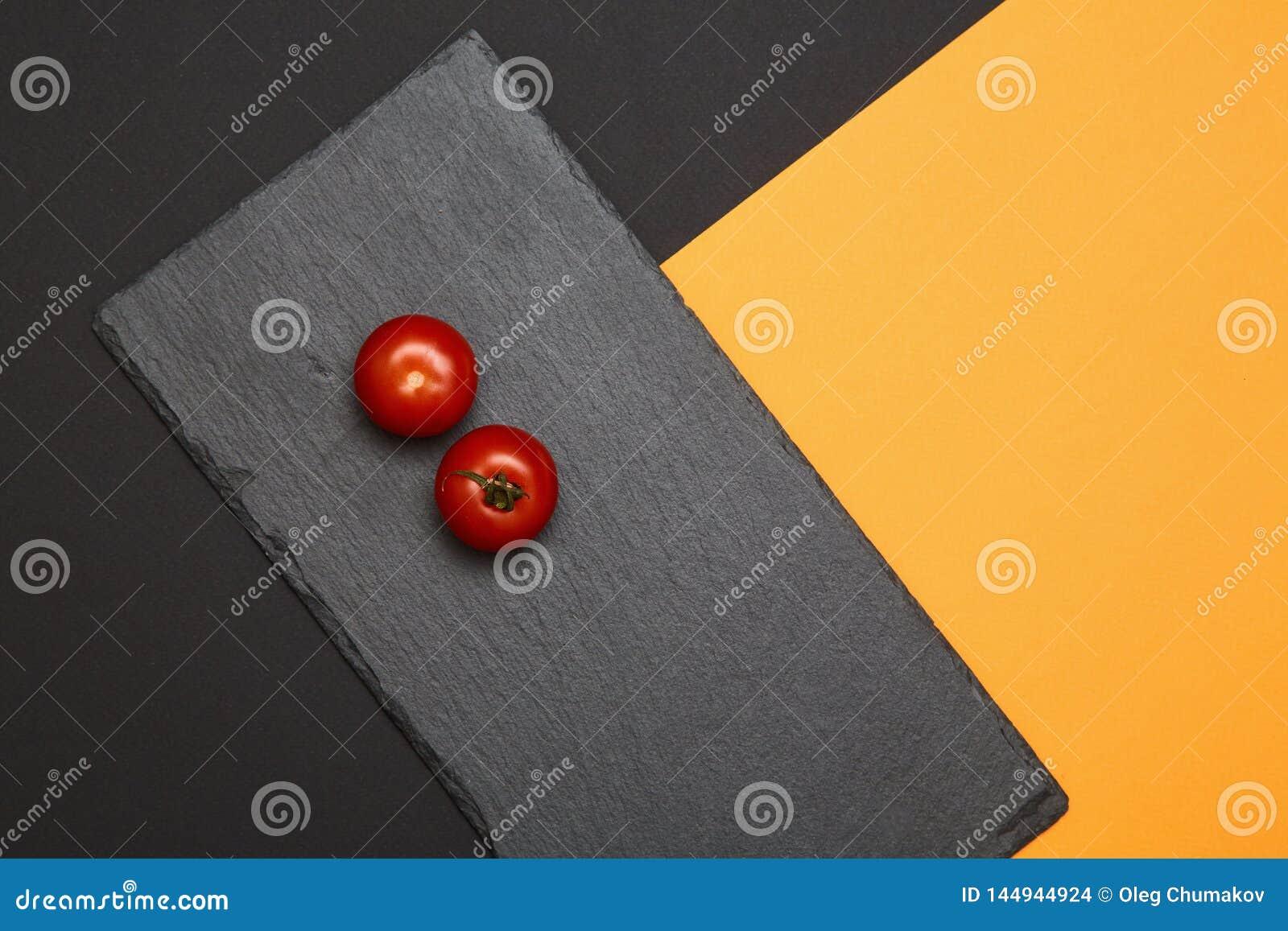 Tomates de cereja maduros compostos em placas pretas da ardósia no fundo colorido
