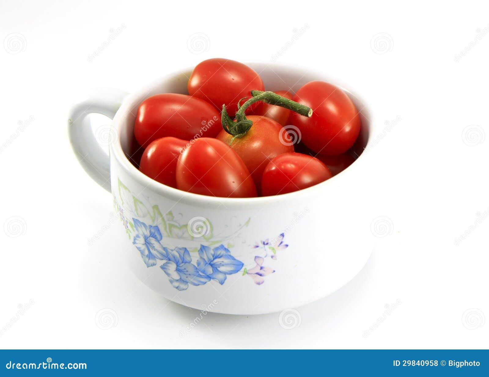Tomates em uma bacia isolada no branco