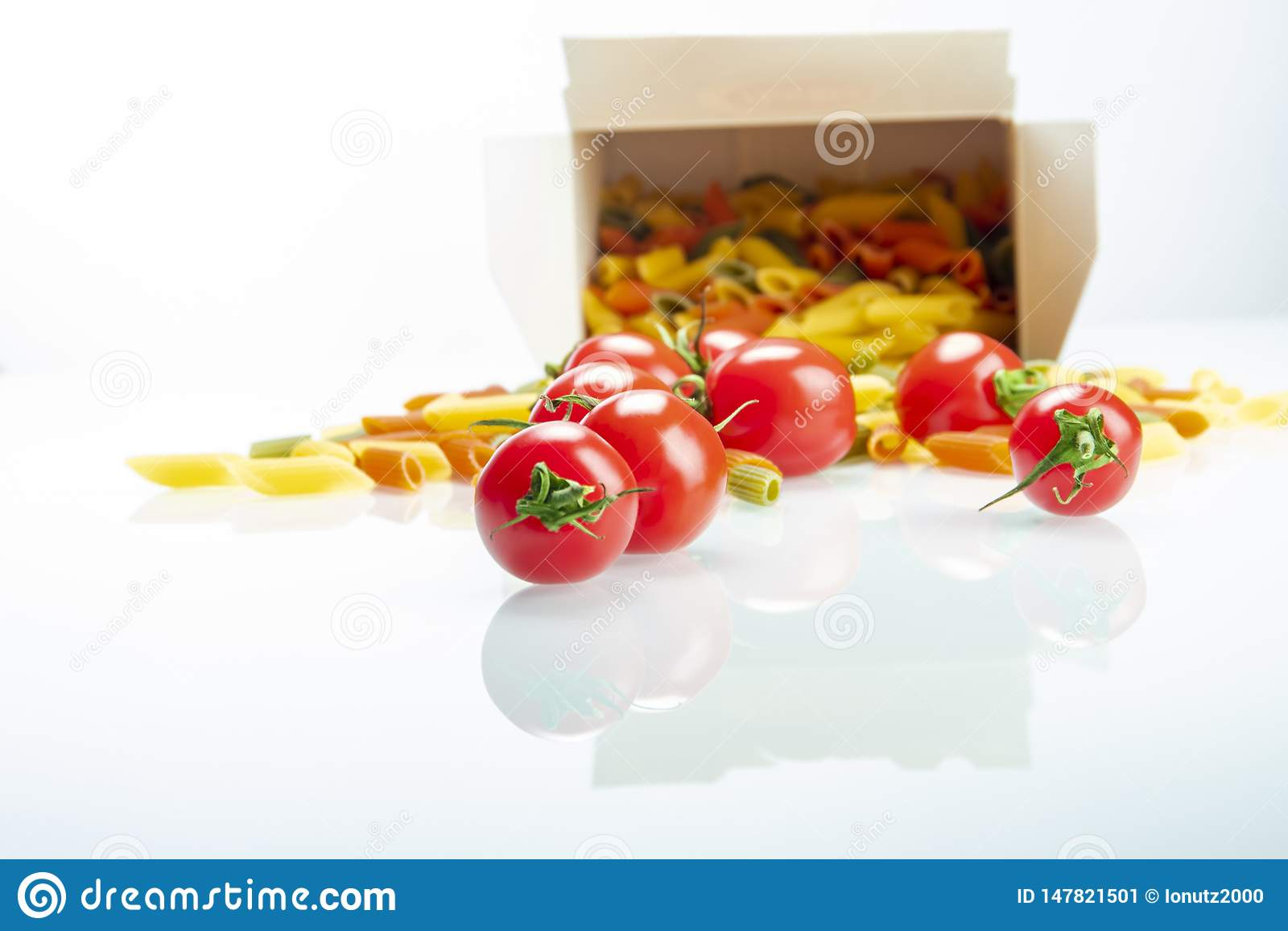 Tomates entre las pastas coloreadas sobre el vidrio reflexivo blanco