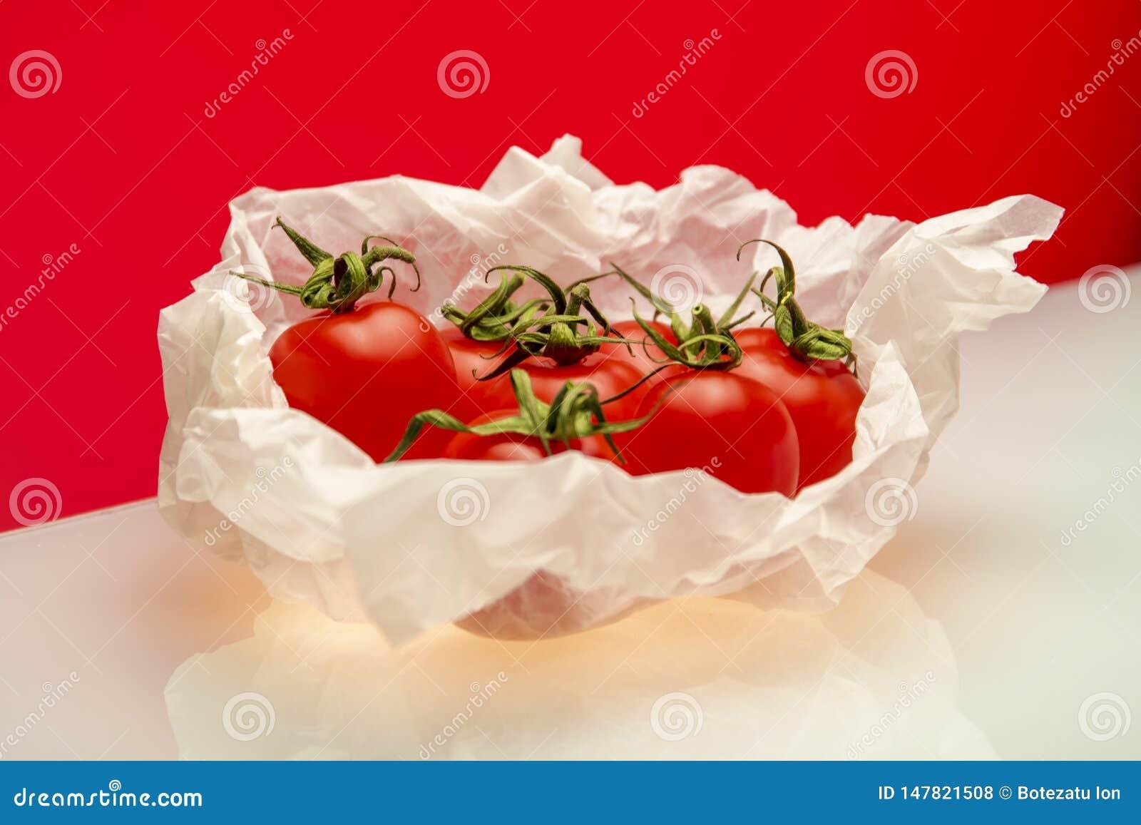 Tomates enveloppées en faisant cuire le papier sur le fond rouge