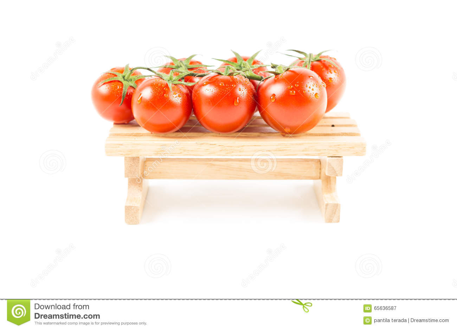 Tomates fraîches de nature avec la vigne verte sur en bois