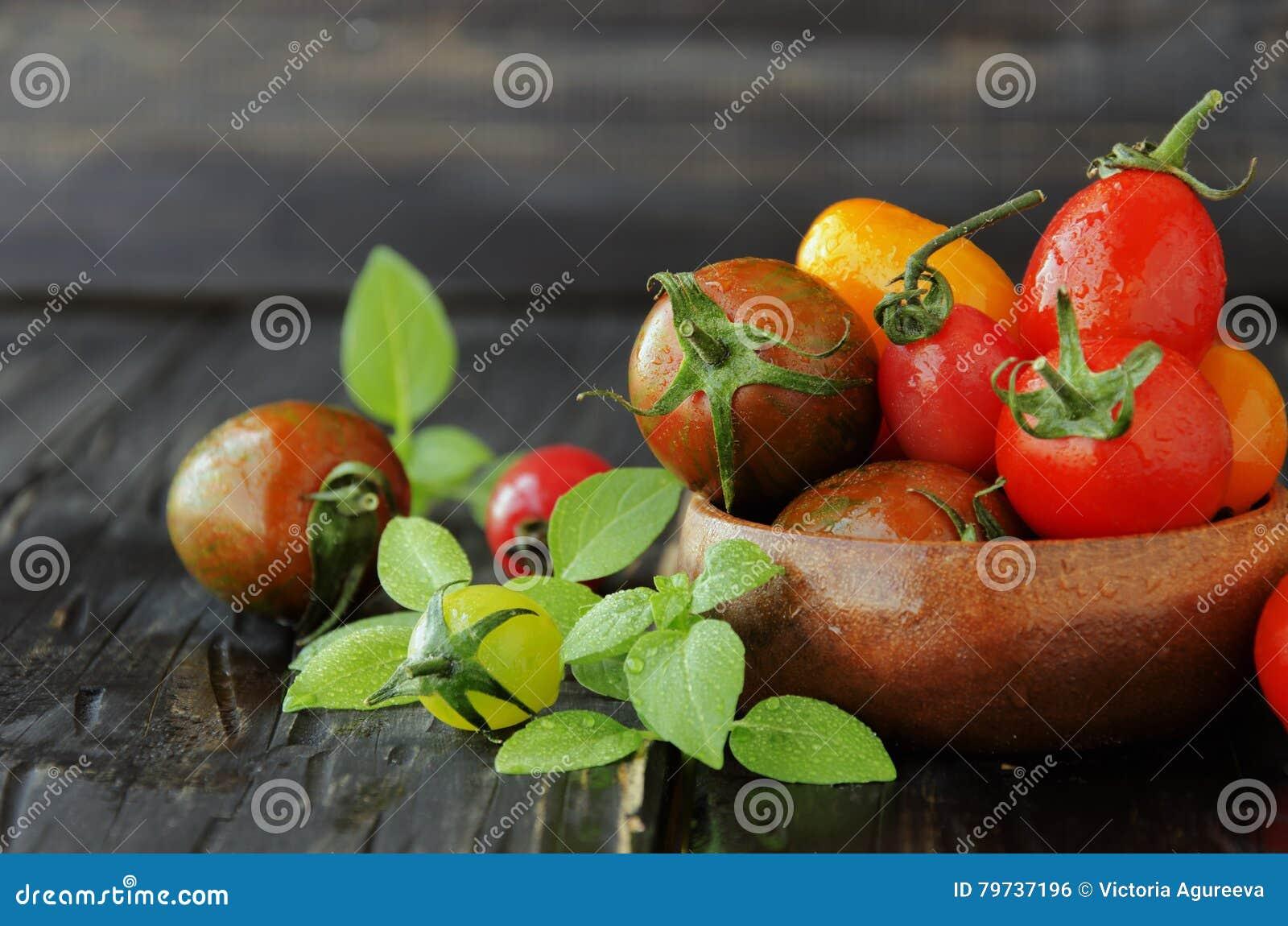 Tomates frescos con albahaca en la tabla de madera, foco selectivo