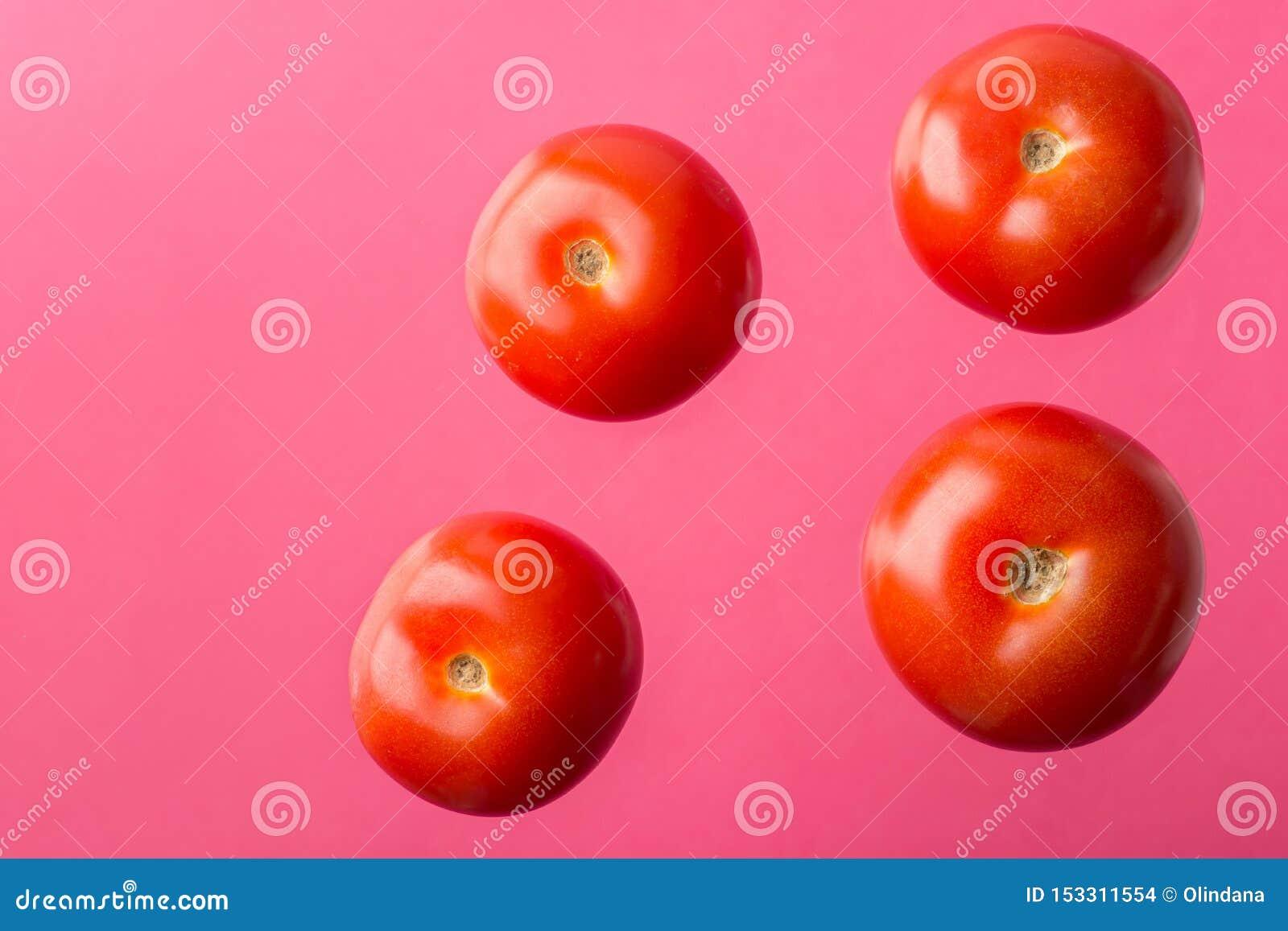Tomates juteuses mûres flottant faire de la lévitation en air sur le fond rose Affiche créative de nourriture pour l alimentation