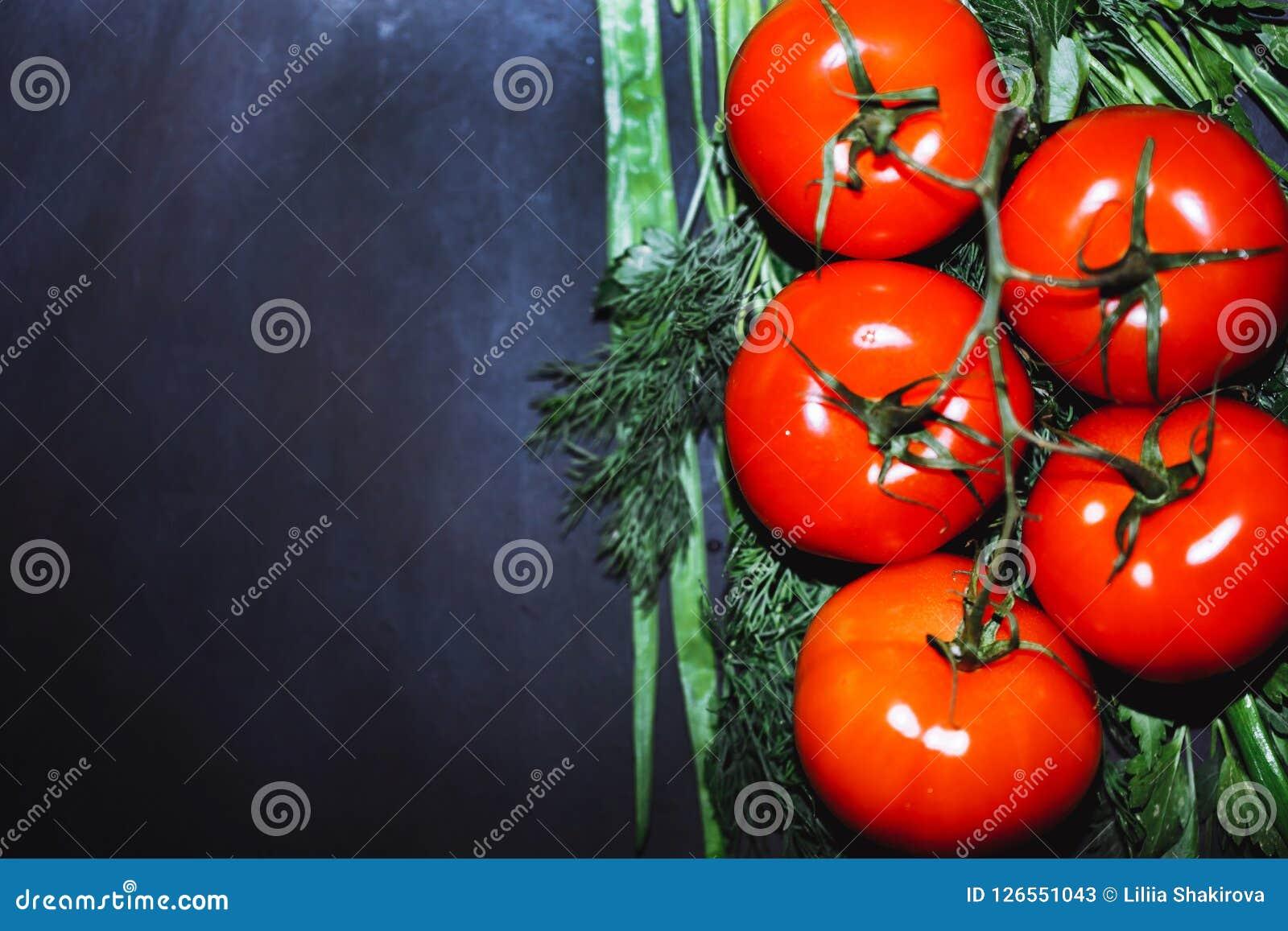 Tomates maduros com as ervas no fundo preto