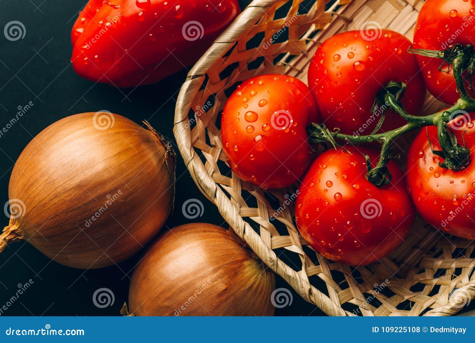 Tomates molhados frescos nas gotas da água, cebola dourada, pimenta de sino, vista superior
