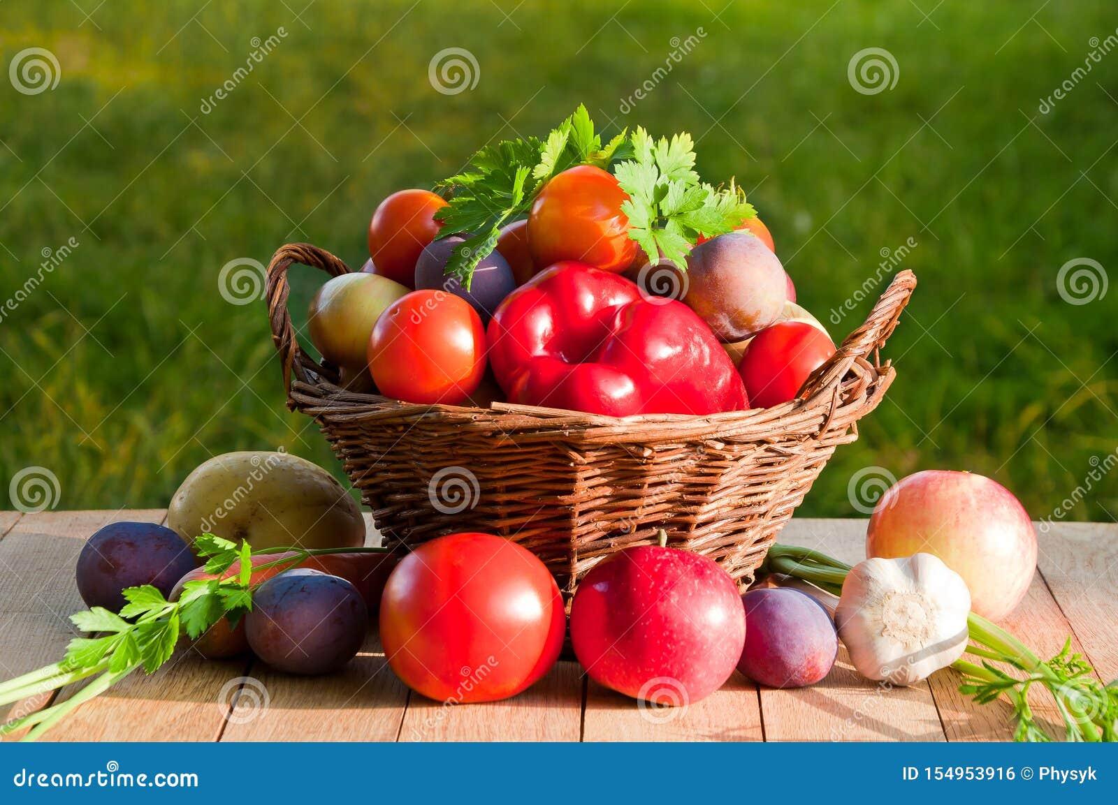 Tomates, pimentas, ameixas, maçãs e outros vegetais e frutos em uma cesta de vime em uma tabela de madeira